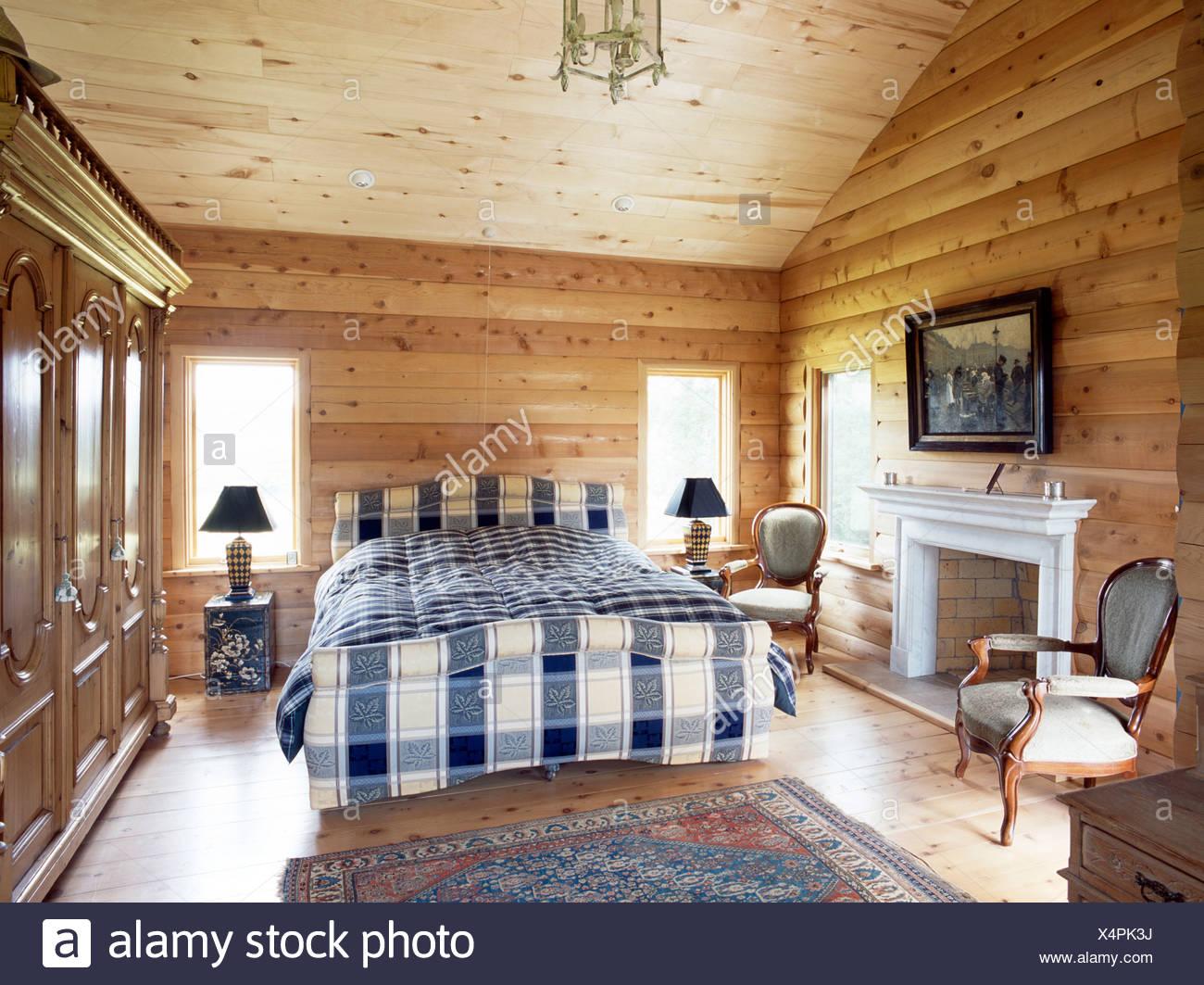 Blaue + Weiße Bettwäsche Auf Bett Im Land Schlafzimmer Mit Kiefern Log  Getäfelten Wände Und Die Decke Kiefer