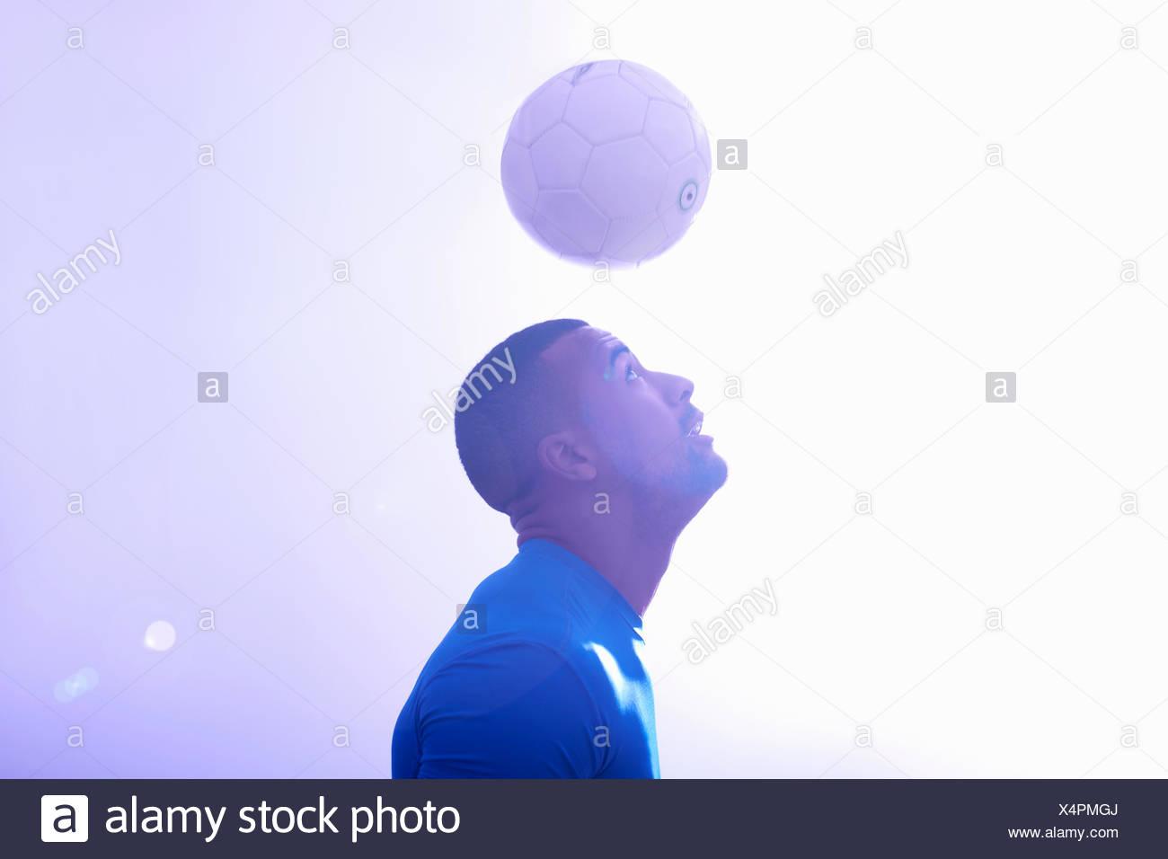 Studioaufnahme des jungen männlichen Fußballer Ball Mitte Luft mit Header halten Stockfoto