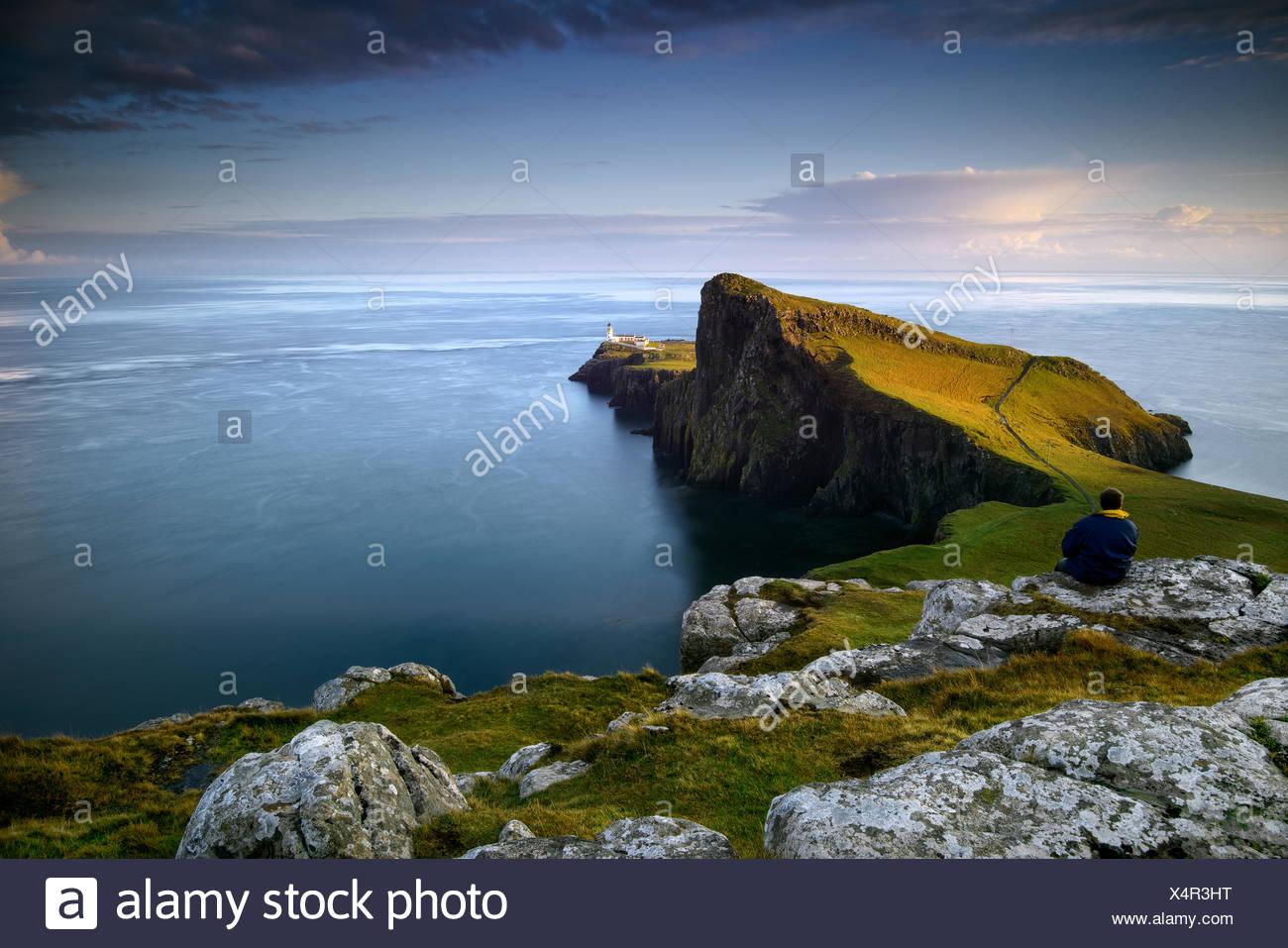 Mitte erwachsenen Mann sitzt auf einem Felsen, Blick auf das Meer in landschaftlich Point, Schottland Stockbild