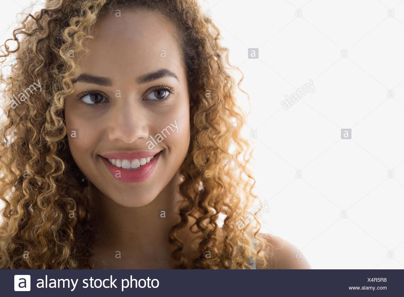 Lächelnde Frau mit lockigem Haar wegschauen Stockbild