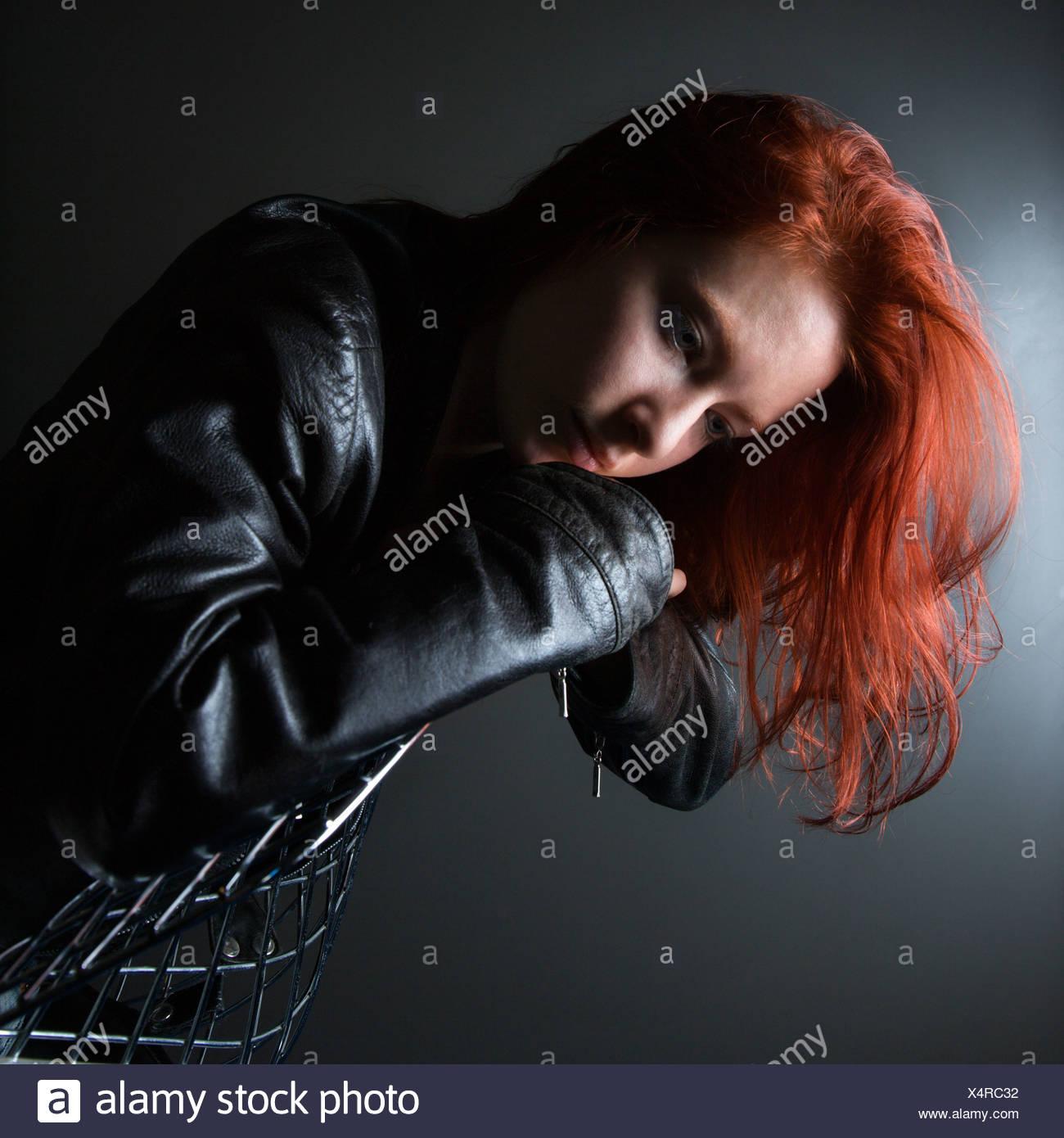 Hübsche rothaarige junge Frau trägt Lederjacke über Rückseite Stuhl hängen Stockfoto