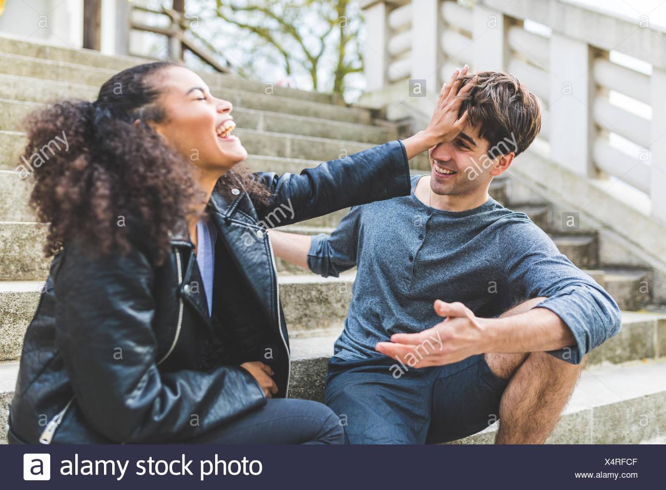 Junge Frau schieben Freund auf der Treppe im Battersea Park Stockbild