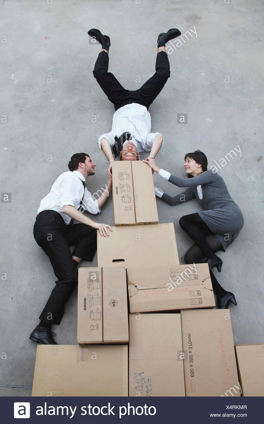 Drei Geschäftsleute auf Pappkartons, Mann tut, Handstand, Lächeln, Porträt, erhöht, Ansicht Stockbild