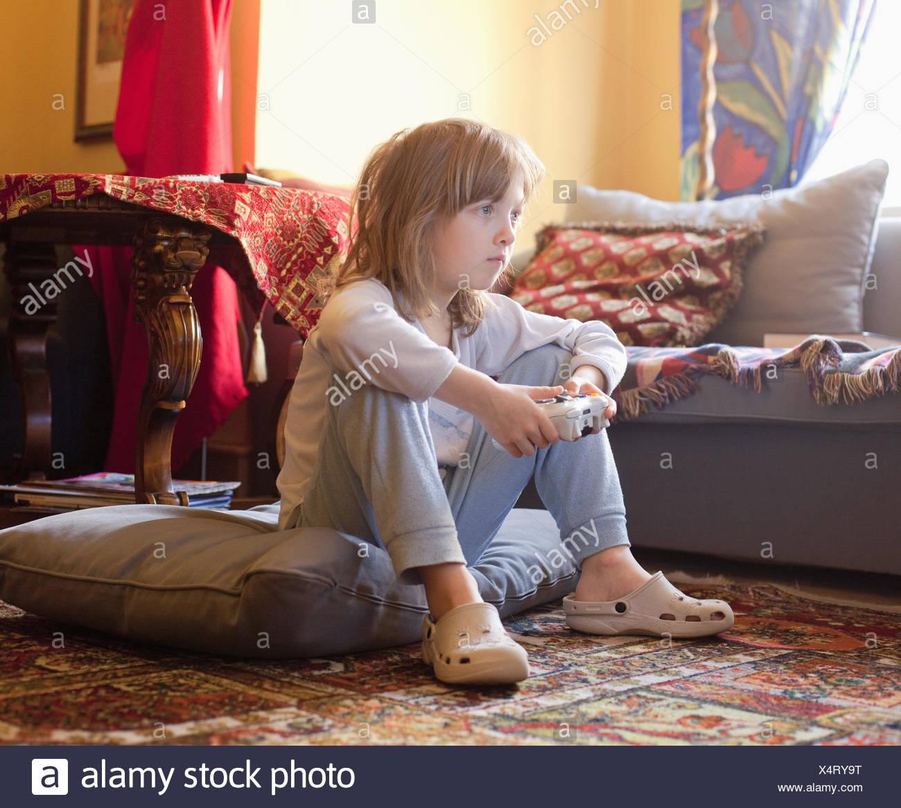 Junge spielt Konsole Spiel auf dem Boden sitzen. Stockfoto