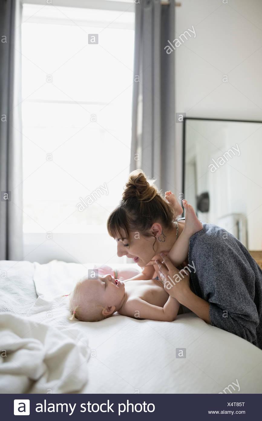 Spielerische Mutter und Tochter von Angesicht zu Angesicht auf Bett Stockbild