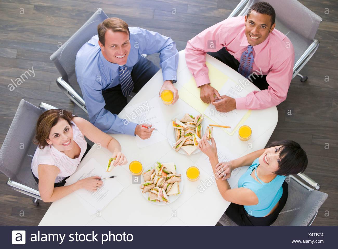 Vier Unternehmer am Konferenztisch mit Sandwiches, Lächeln Stockbild