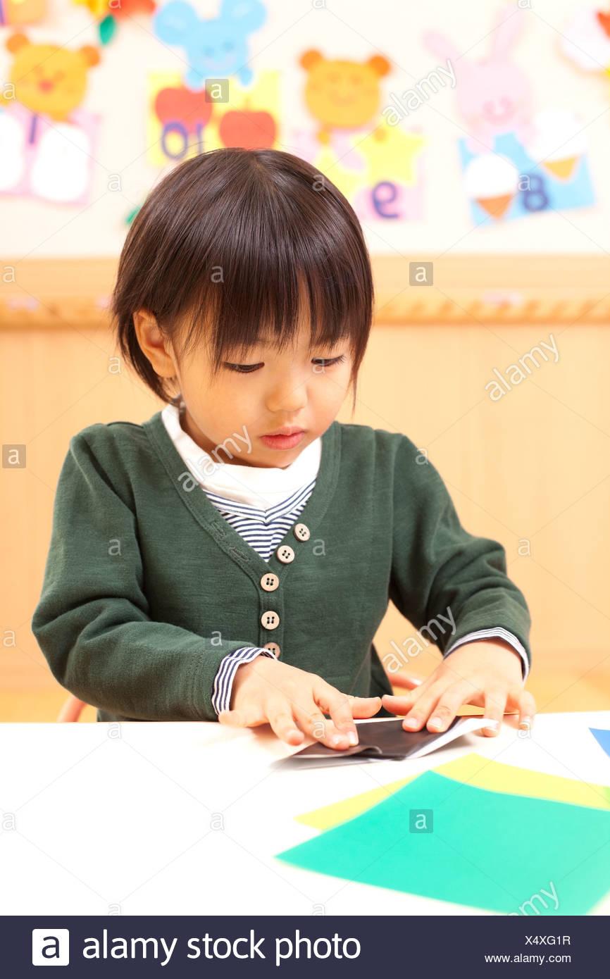 Jungen spielen Origami Stockbild