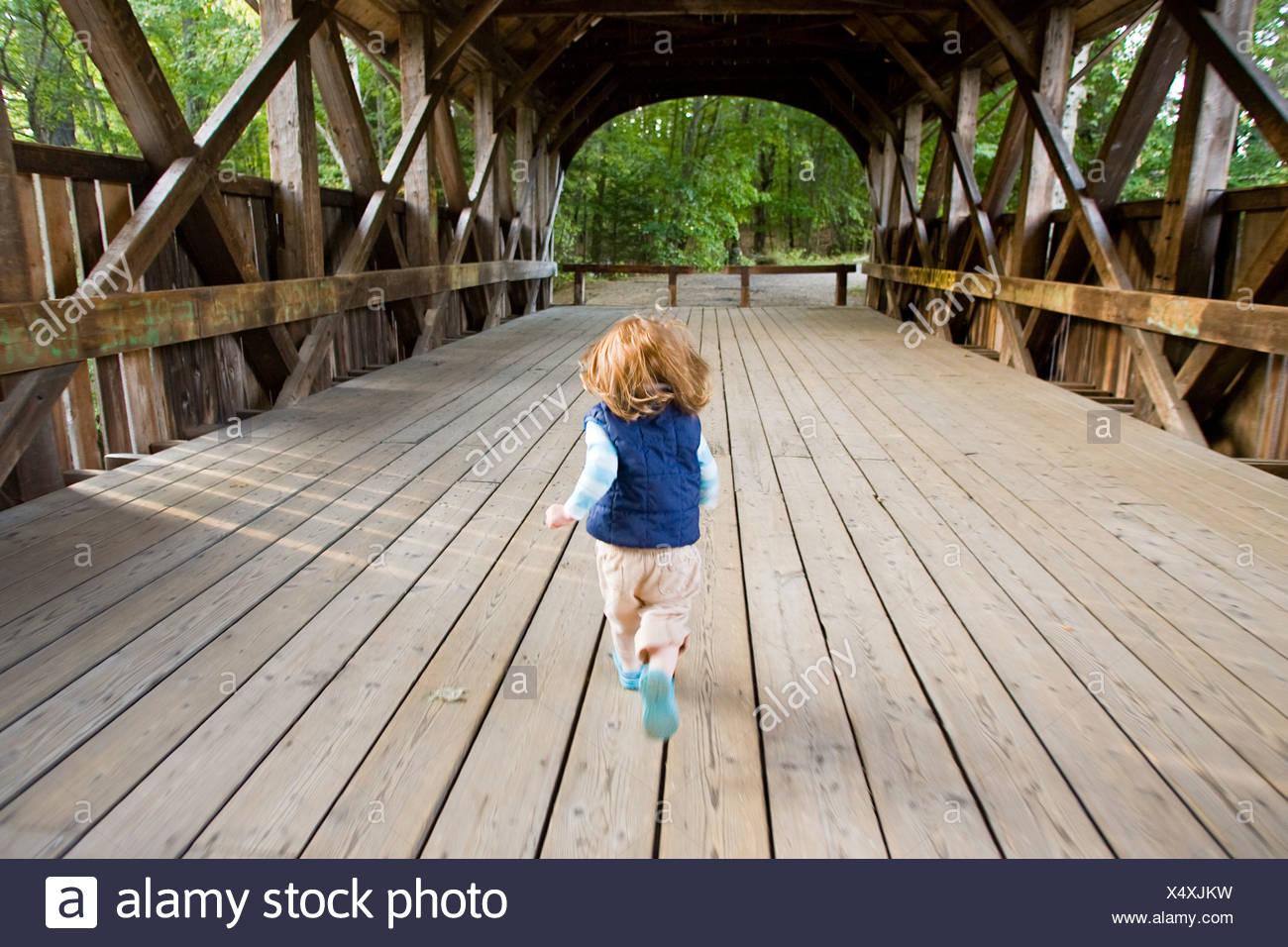 Ein kleines Mädchen läuft über eine überdachte Brücke. Stockbild