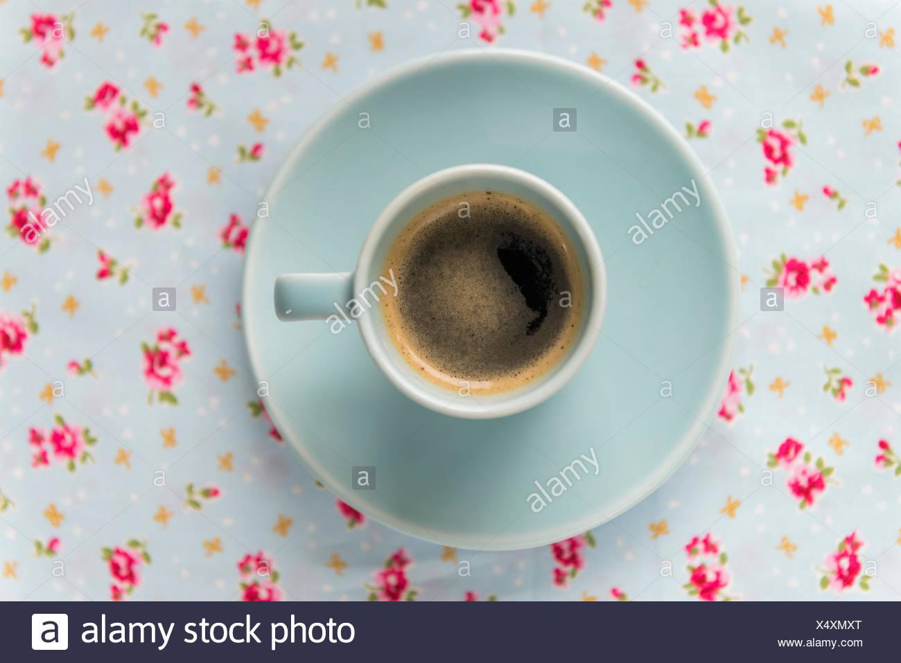 Espresso-Kaffeemaschine in einem blauen Tasse und Untertasse auf einer floral Tischdecke. Stockbild