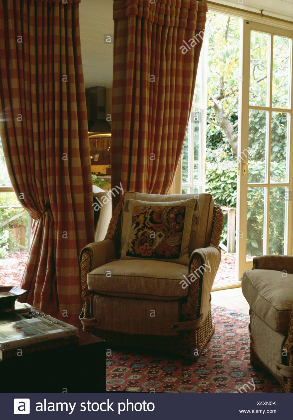 Beige Sessel vor rote aufgegebenes Vorhänge bei Fenstertüren im Land ...