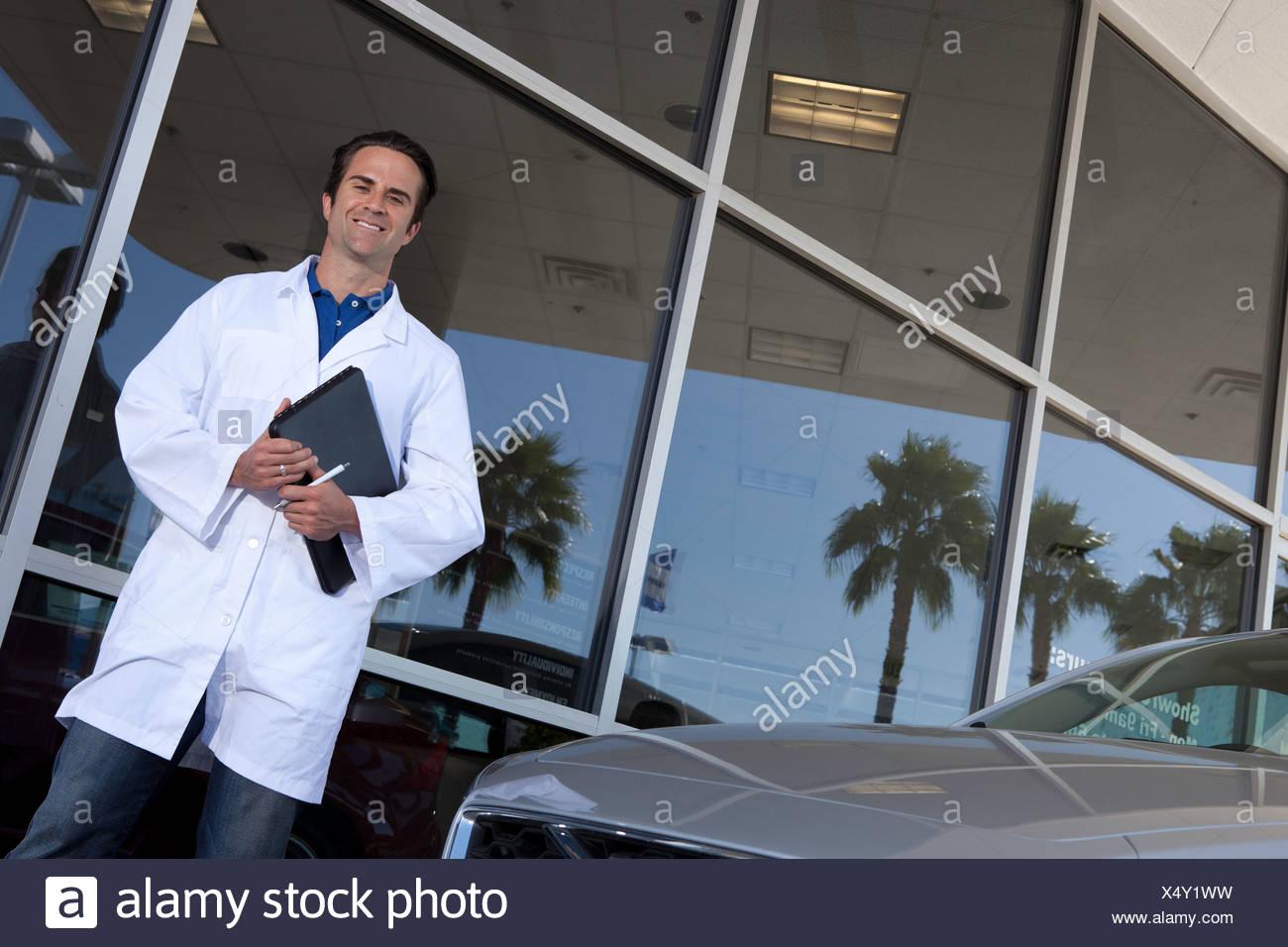 Glücklich Autohändler vor Autohaus Stockbild