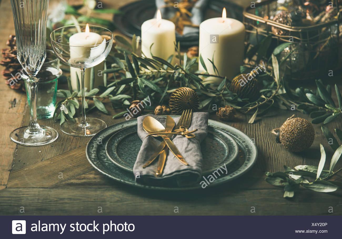 Weihnachten oder Silvester Urlaub Tabelle einstellen. Teller, Besteck, Gläser, Kerzen, Olivenzweige und Spielzeug festliche Dekorationen über vintahge Tab Stockbild