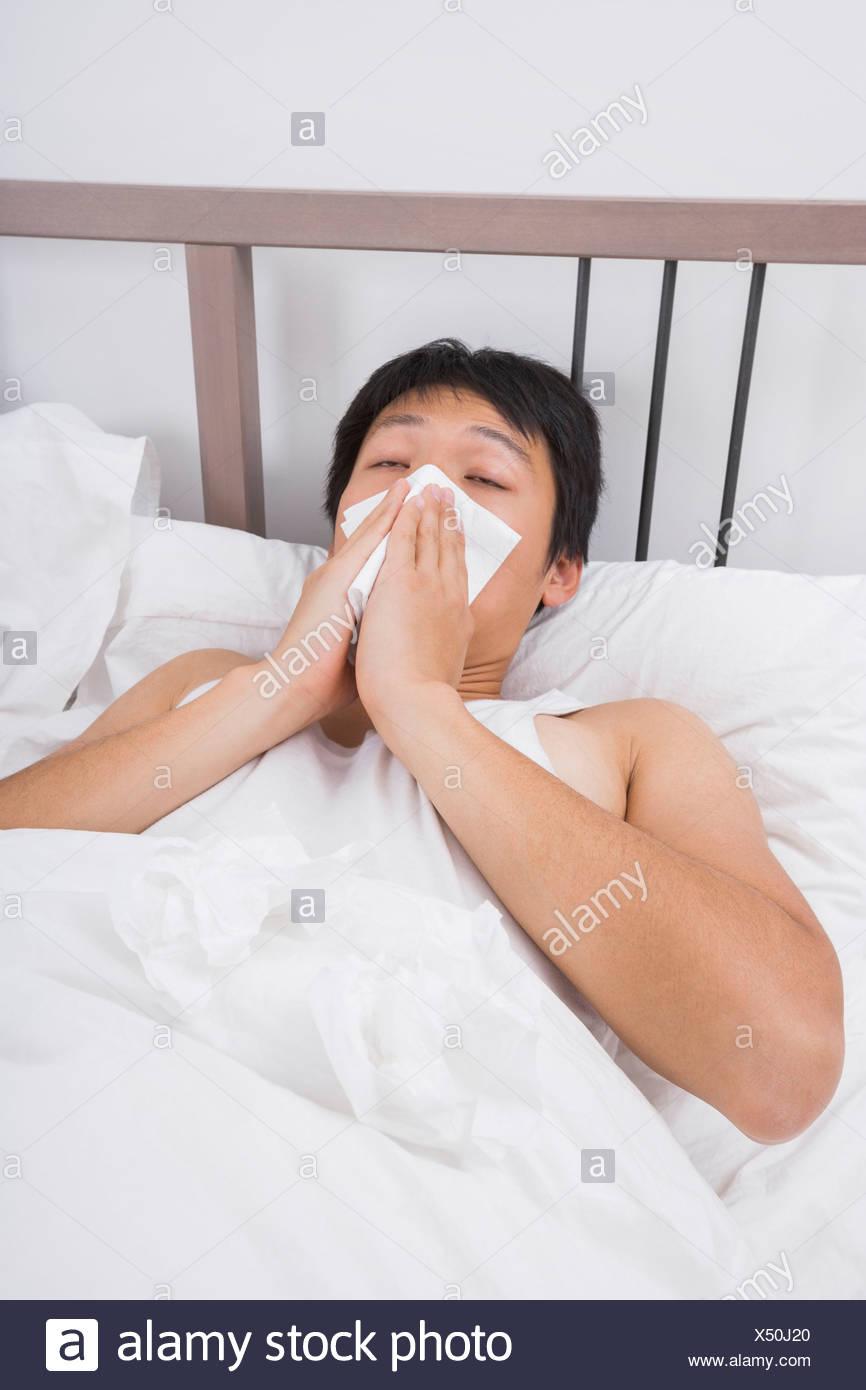 Asiatischer Mann Nase weht im Bett Stockbild