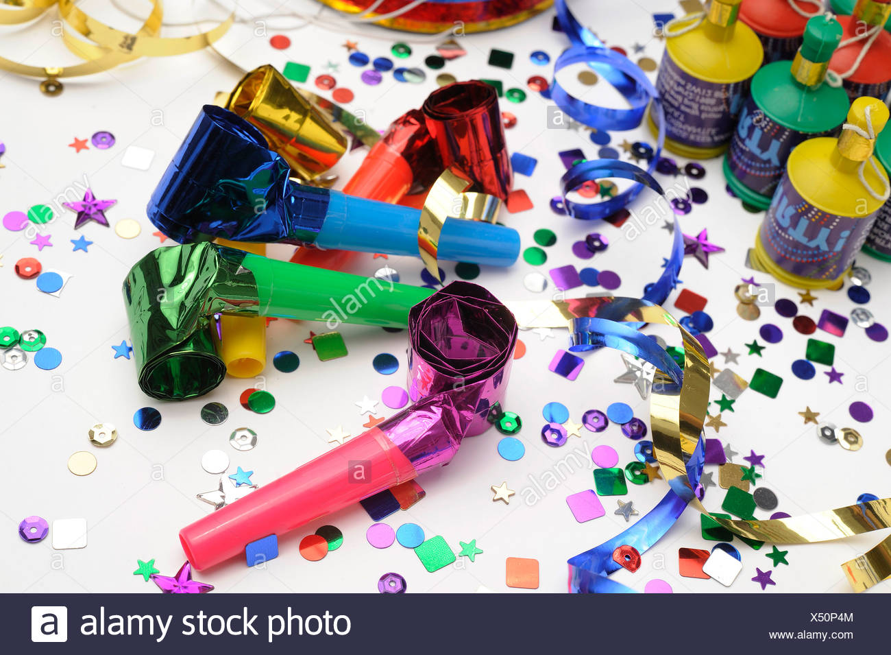 Ein Stillleben Bild der bunte Konfetti, Horn Gebläse, Luftschlangen und Party Poppers auf weißem Hintergrund Stockbild