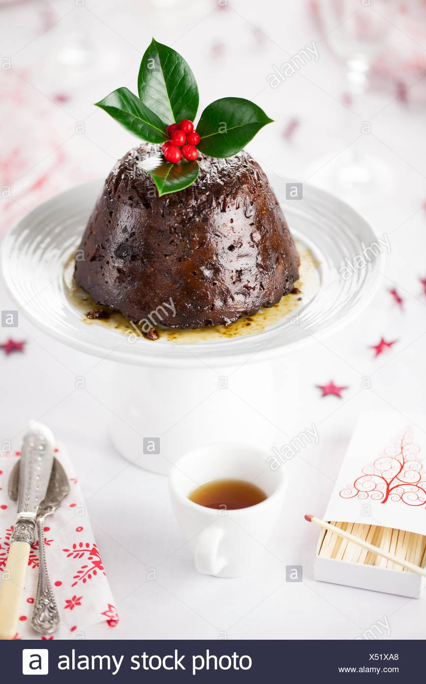 Christmas Pudding mit Schnaps auf eine Tortenplatte. Stockfoto