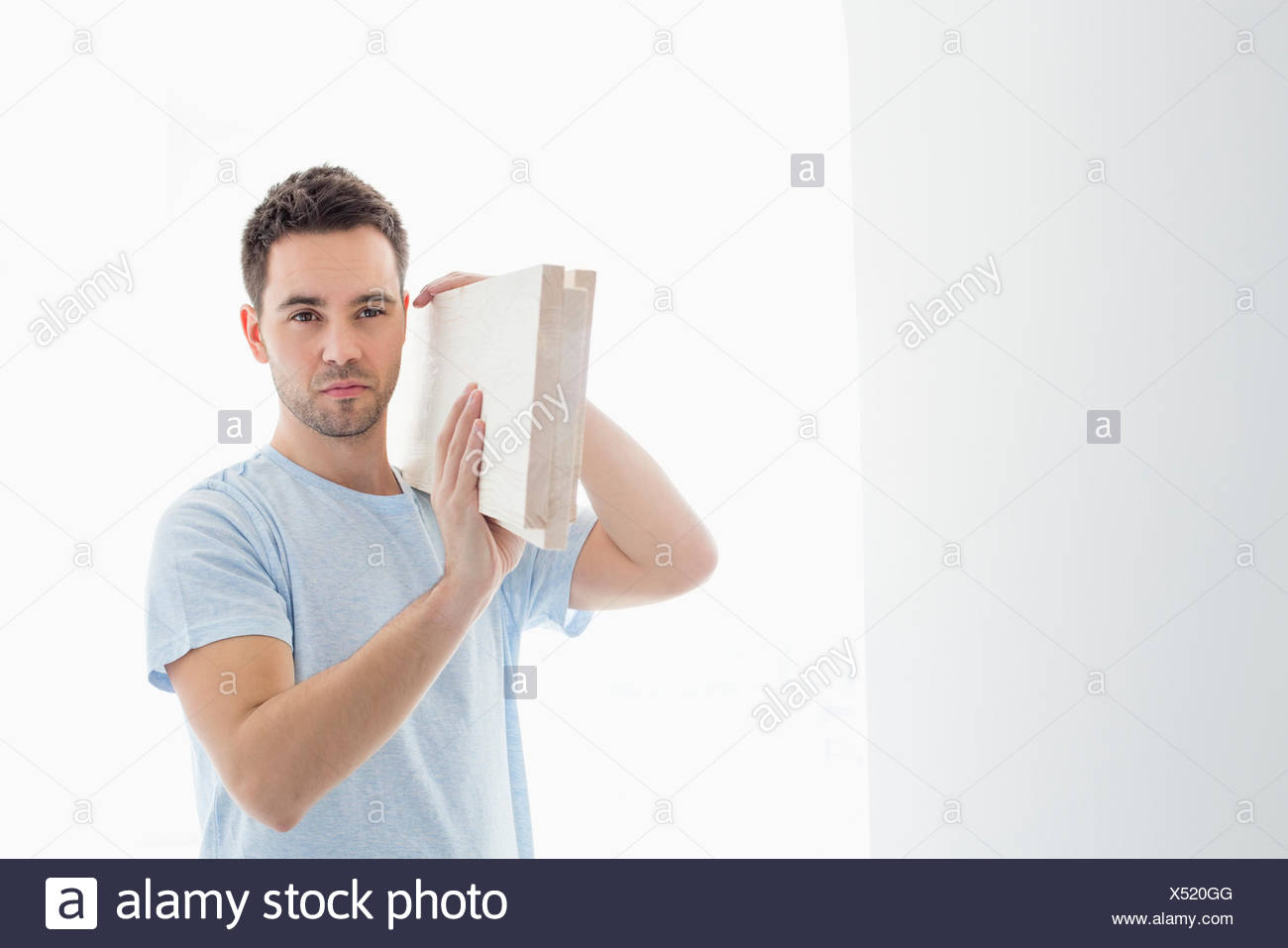 Mid-Adult Mann mit Bauholz auf Schulter Stockbild