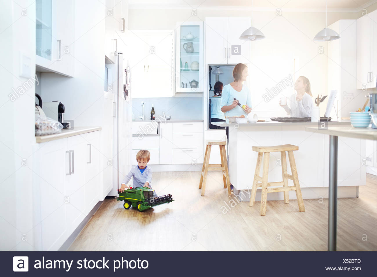 Frauen in Küche kochen, während junge mit Spielzeug-Traktor auf Etage spielt Stockfoto