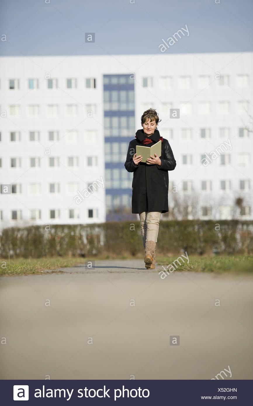 Frau zu Fuß und Lesung Stockbild