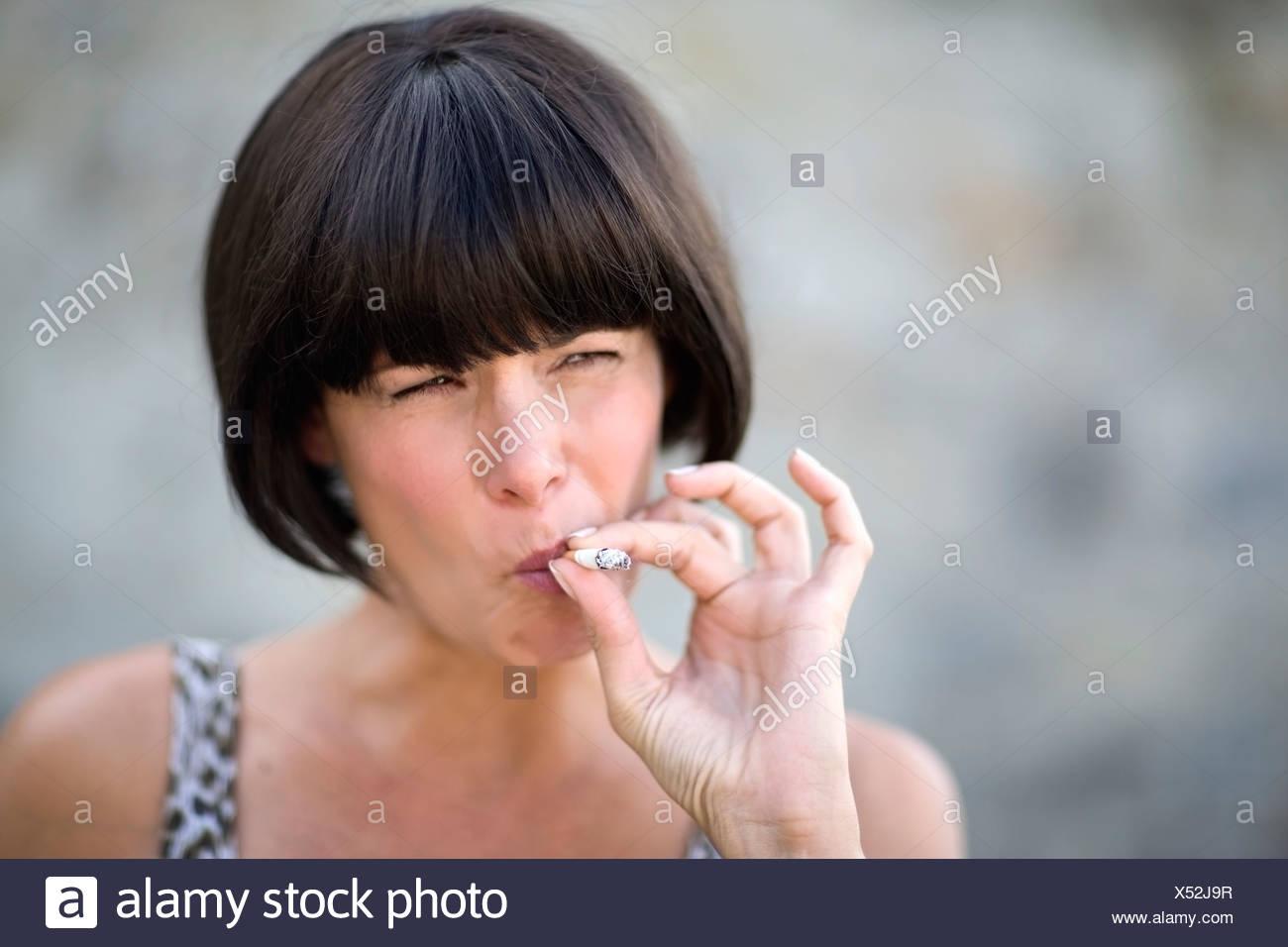 Frau raucht eine Zigarette Stockbild