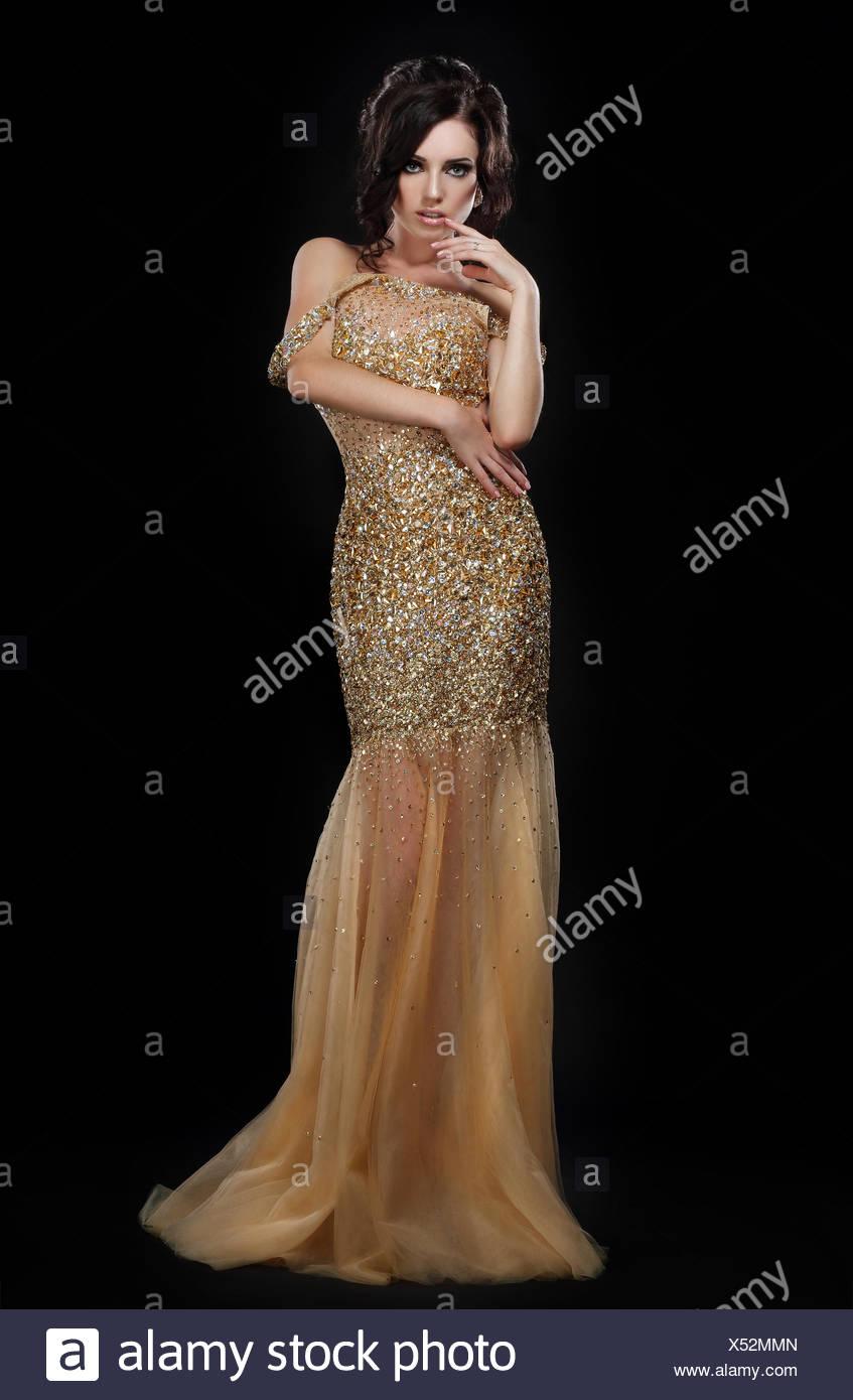 Formale Partei. Glamouröse Mode-Modell in eleganten goldenen Kleid ...