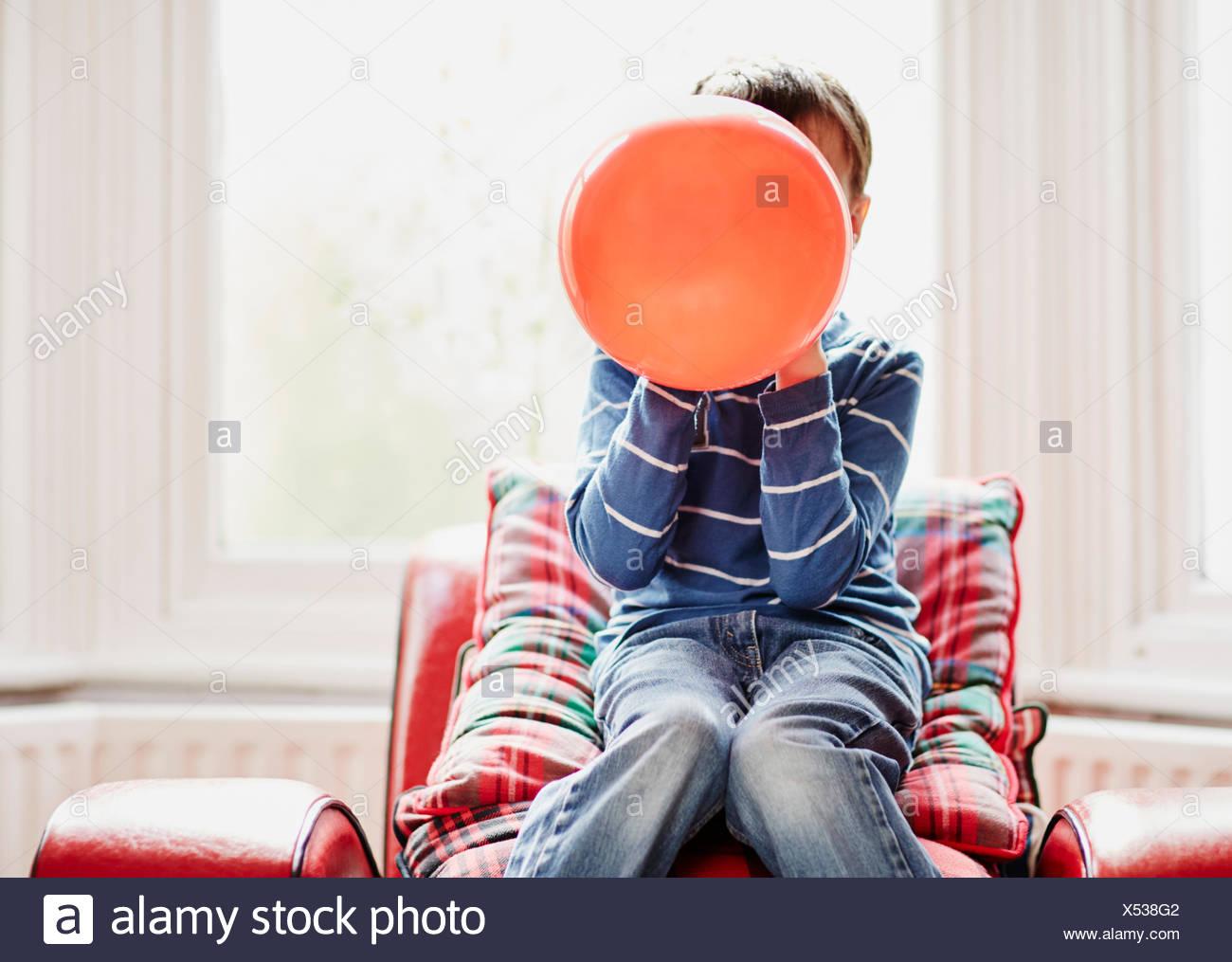 Kleiner Junge hält Ballon vor Gesicht Stockbild