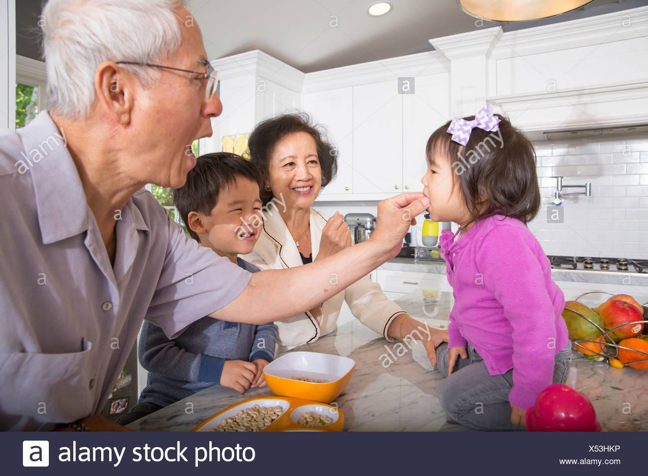 Großvater Fütterung Snack Kleinkind Enkelin in Küche Stockbild
