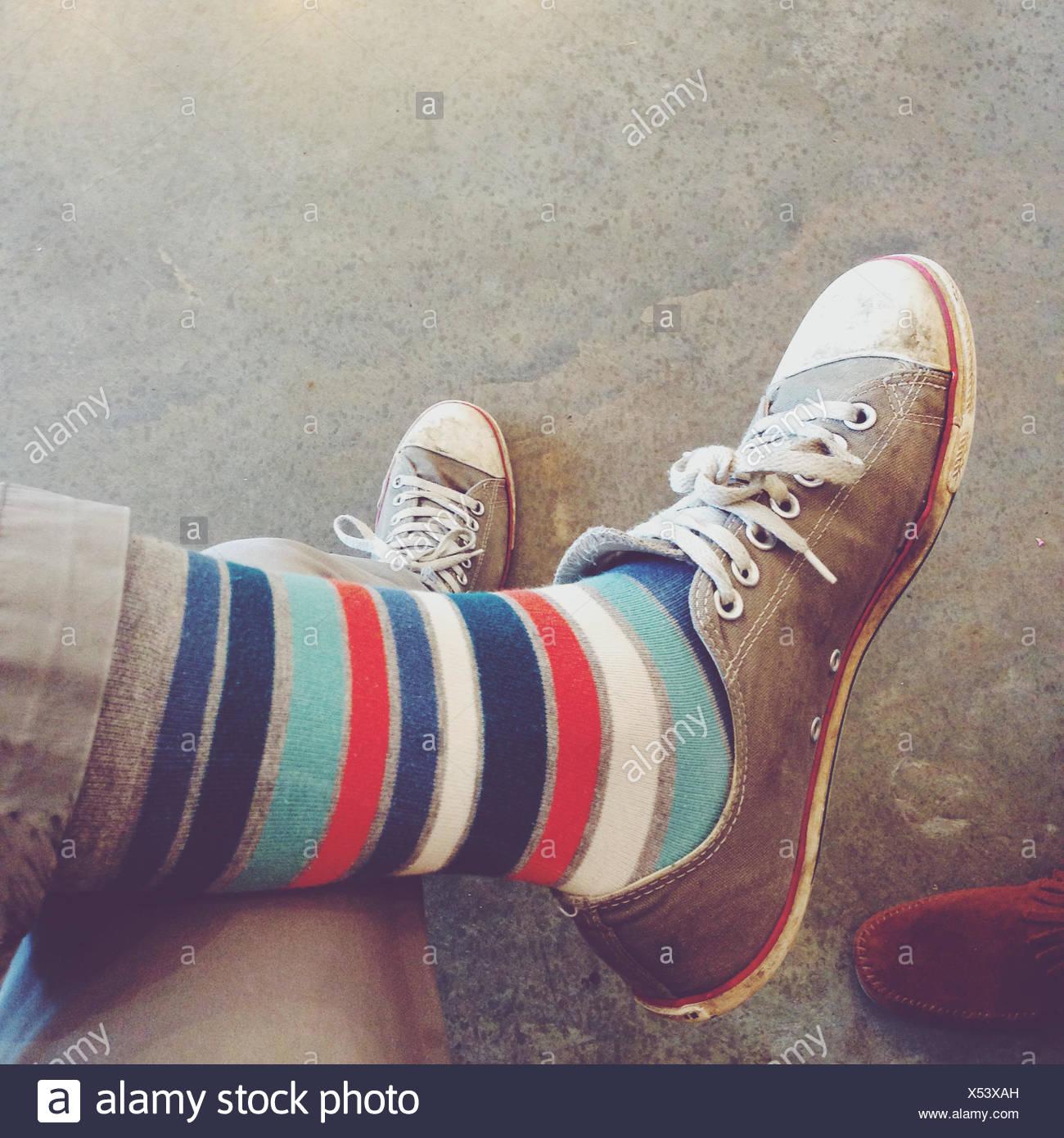 Nahaufnahme einer Person, die gestreifte Socken und Sportschuhe trägt Stockfoto