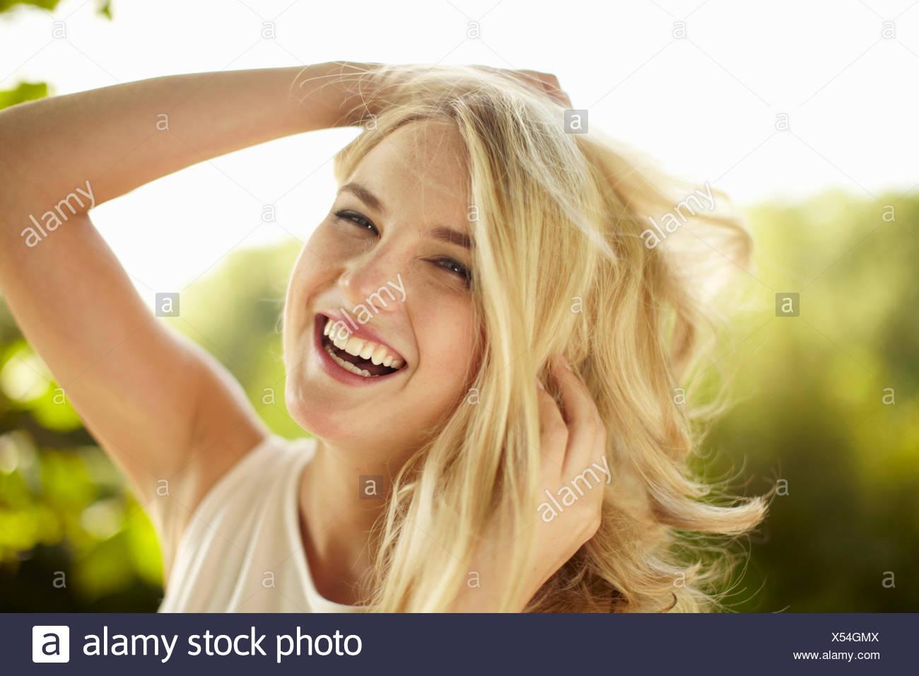 Junge Frau lachend mit Hände in ihr Haar im park Stockbild