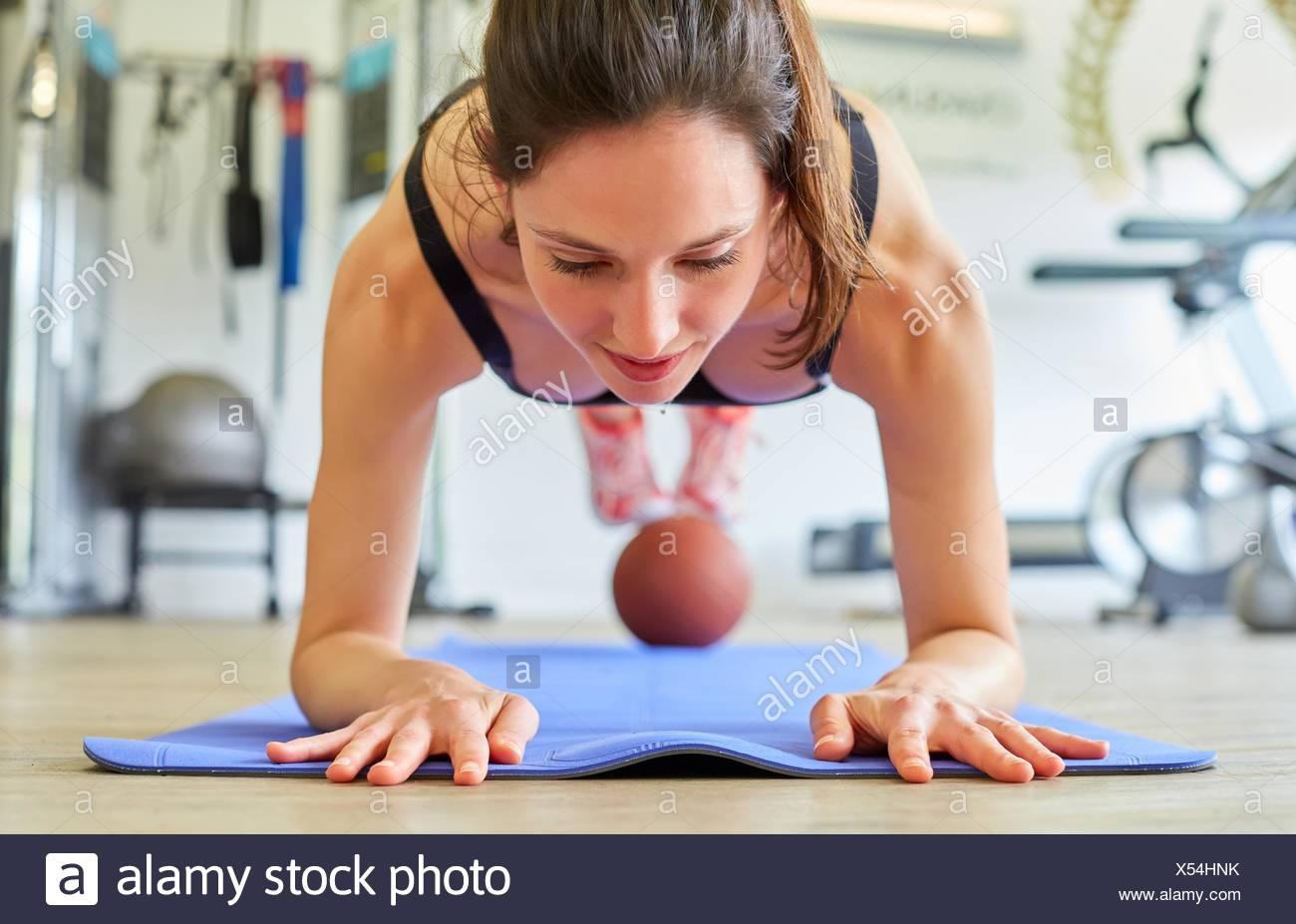 Frau macht Liegestütze mit Ball im Fitness-Studio Stockbild