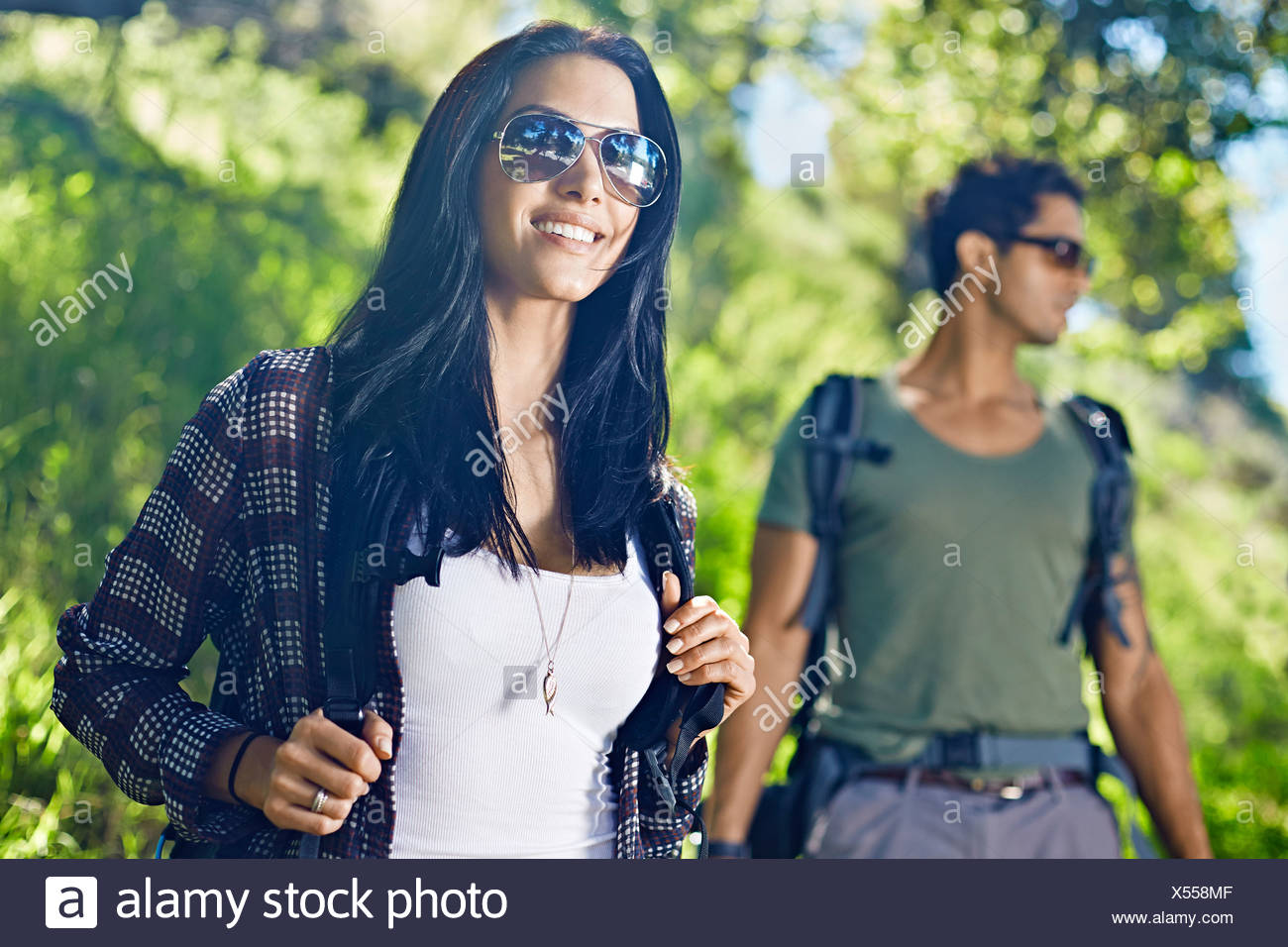 Paare, die mit den Rucksäcken im Wald Stockbild