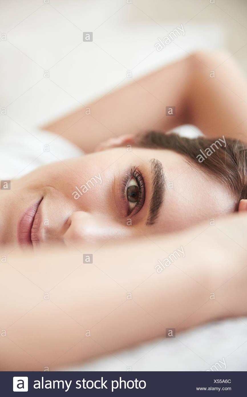 Porträt der schönen jungen Frau auf Bett liegend hautnah Stockbild