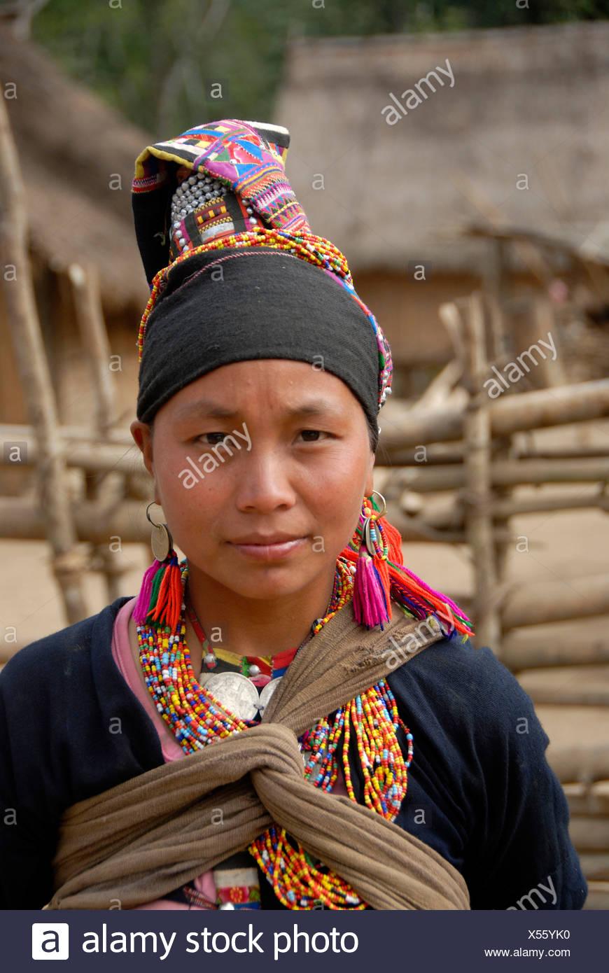 Porträt der jungen Frau der Akha Loma Volksgruppe, schwarzen Tracht, bunt bestickt, Cap, bunte Ketten Stockbild
