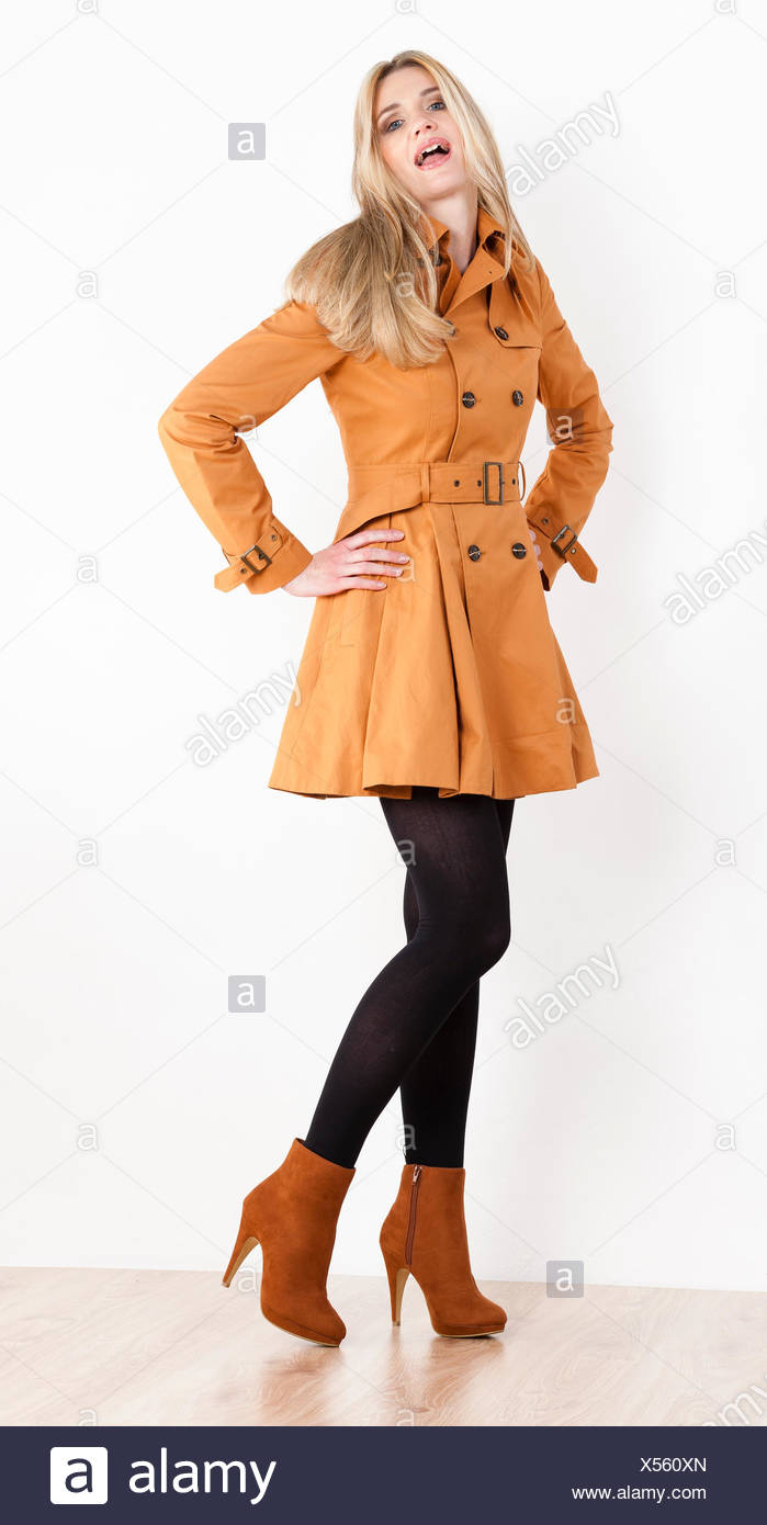 stehende Frau mit Mantel und modische braune Schuhe