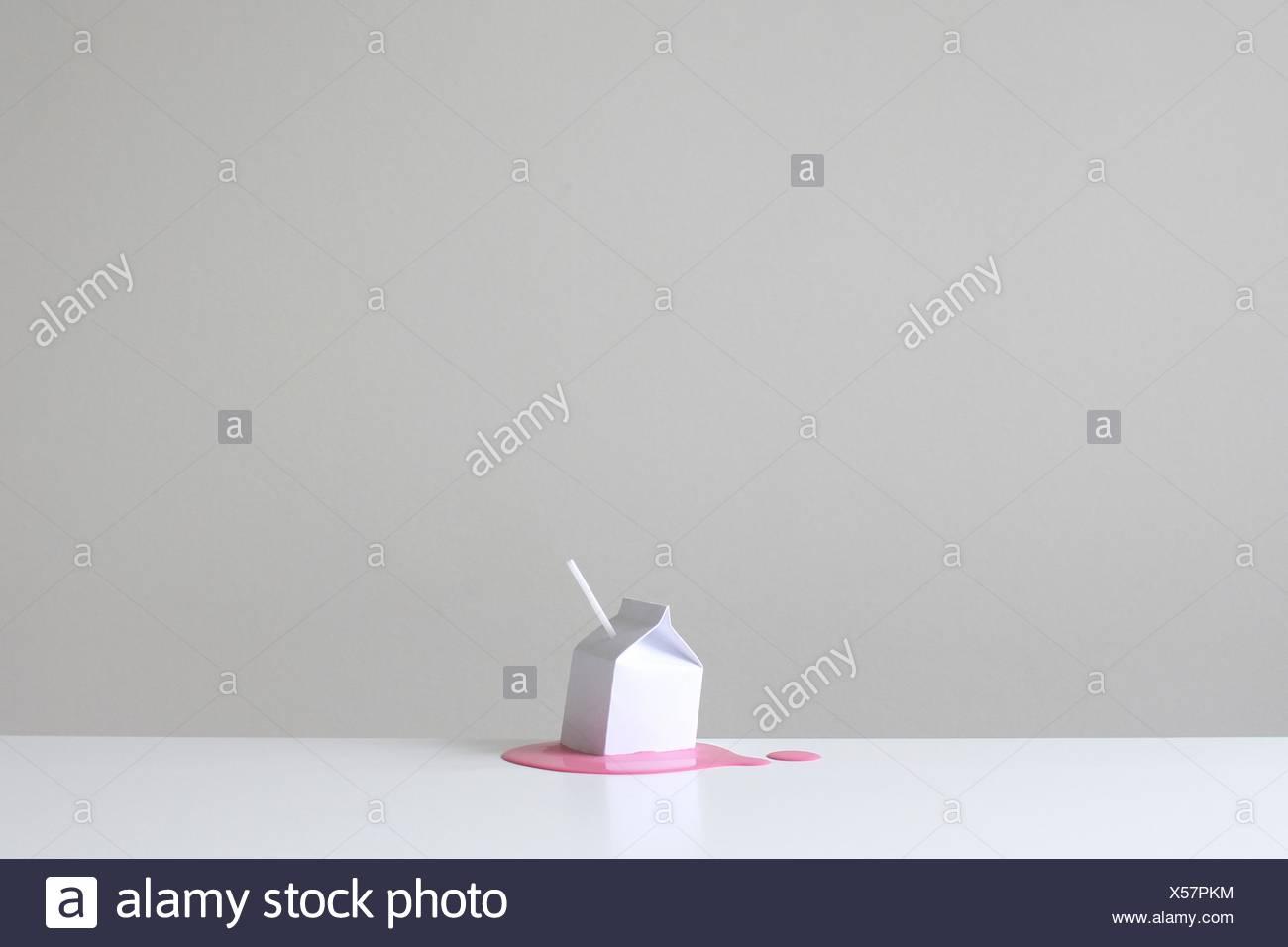 Konzeptionelle Milchtüte mit Stroh auf einen Pool von rosa Erdbeer Milch Stockbild
