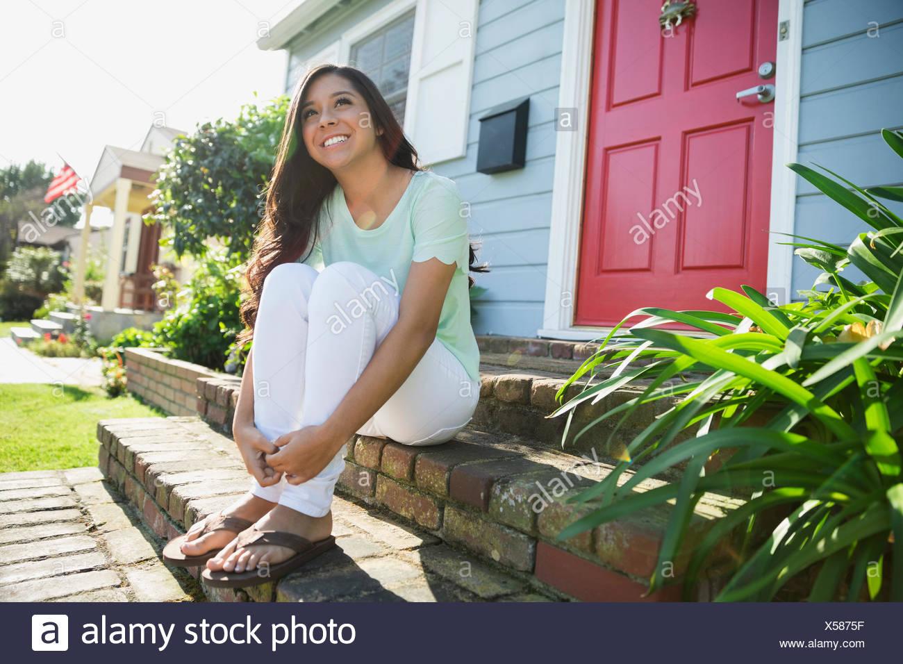 Lächelnde Brünette Teenager-Mädchen sitzen sonnigen vorderen stoop Stockbild