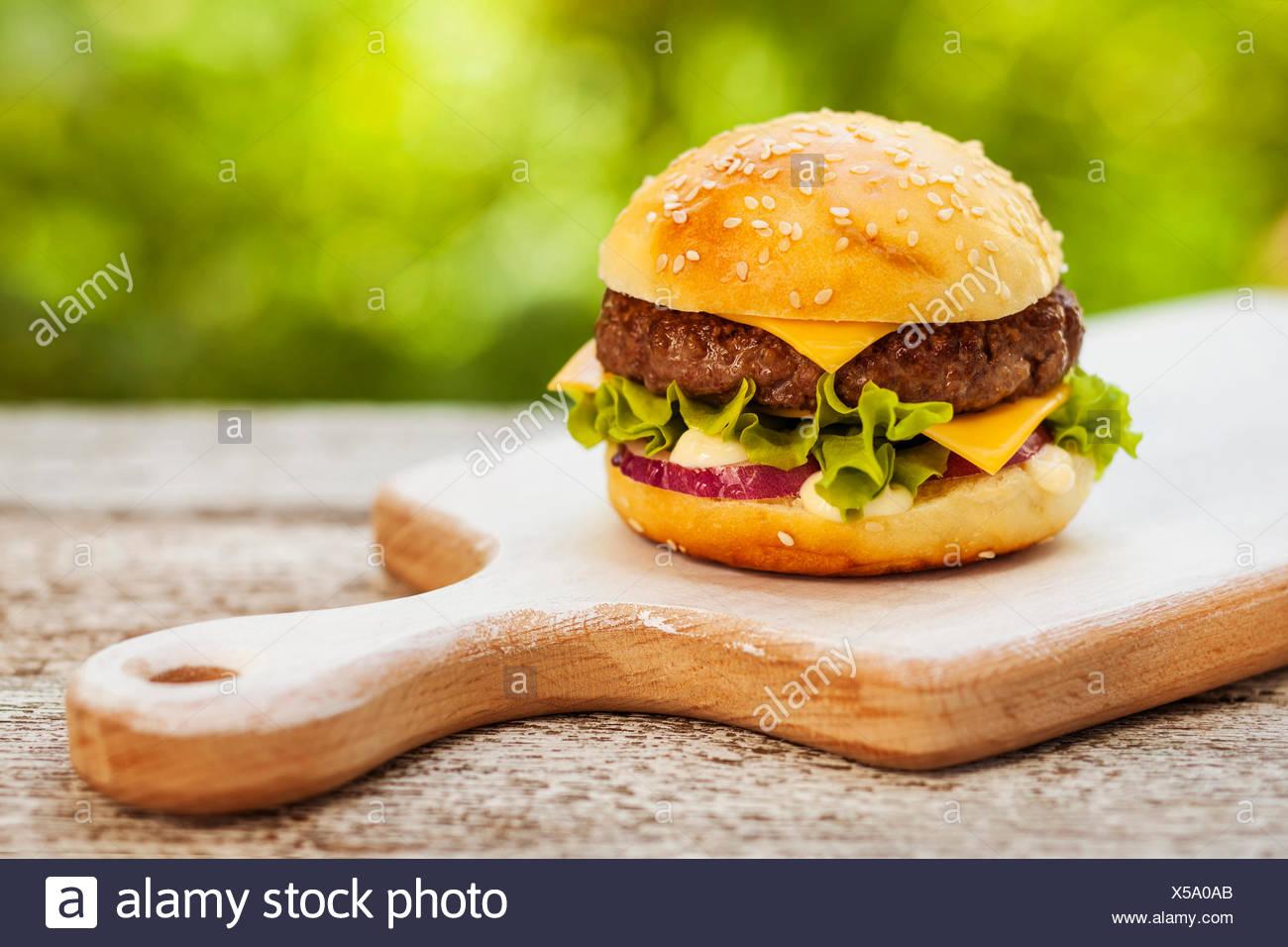 Lecker Burger mit Käse, Salat, Zwiebeln und Tomaten serviert auf einem Holztisch im freien Stockbild