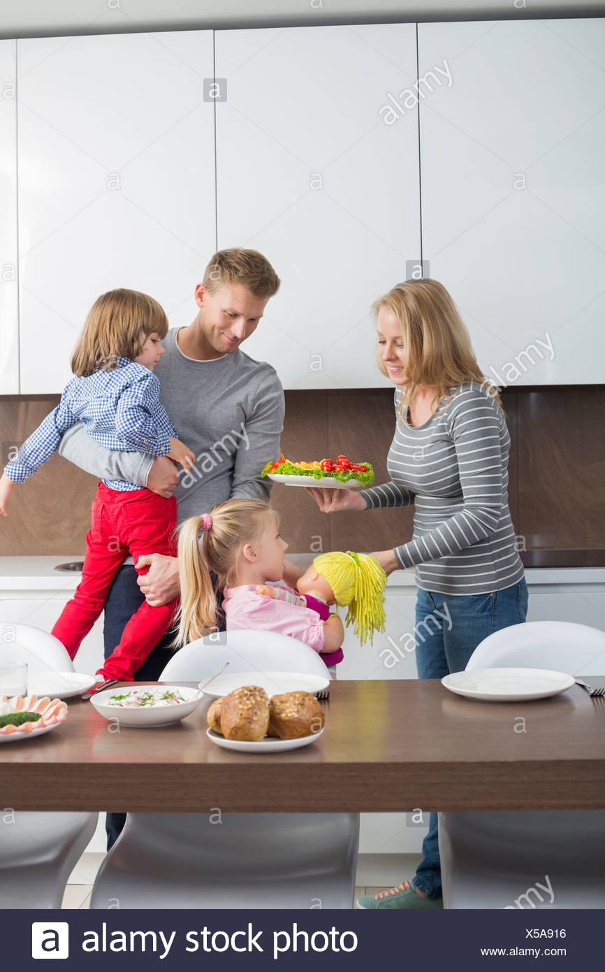 Glückliche Familie mit Kindern, die mit Essen in der Küche Stockbild