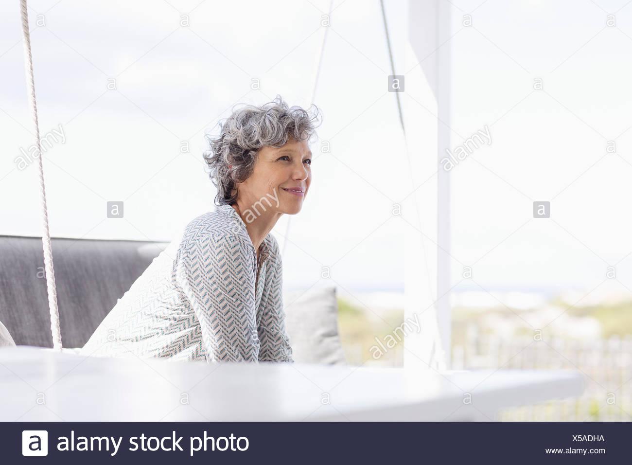 Frau sitzt auf einer Schaukel und Tagträumen Stockbild
