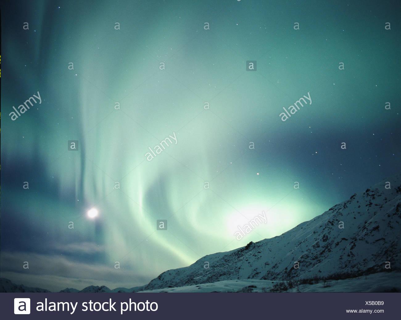 Aurora mit Rising Moon über den Talkeetna Bergen, Alaska Stockfoto