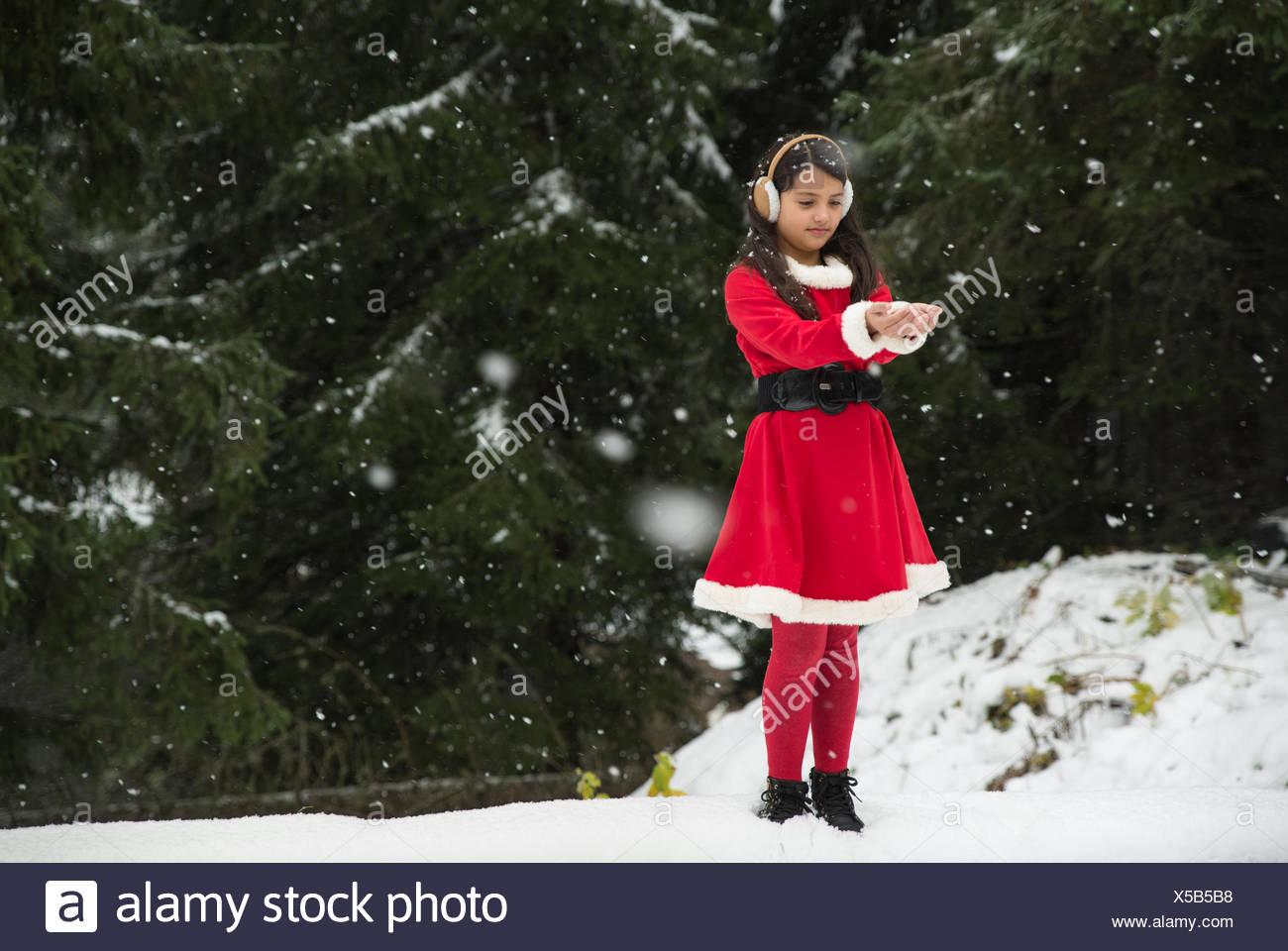 Mädchen mit Weihnachten Santa Outfit fangen Schnee Stockfoto