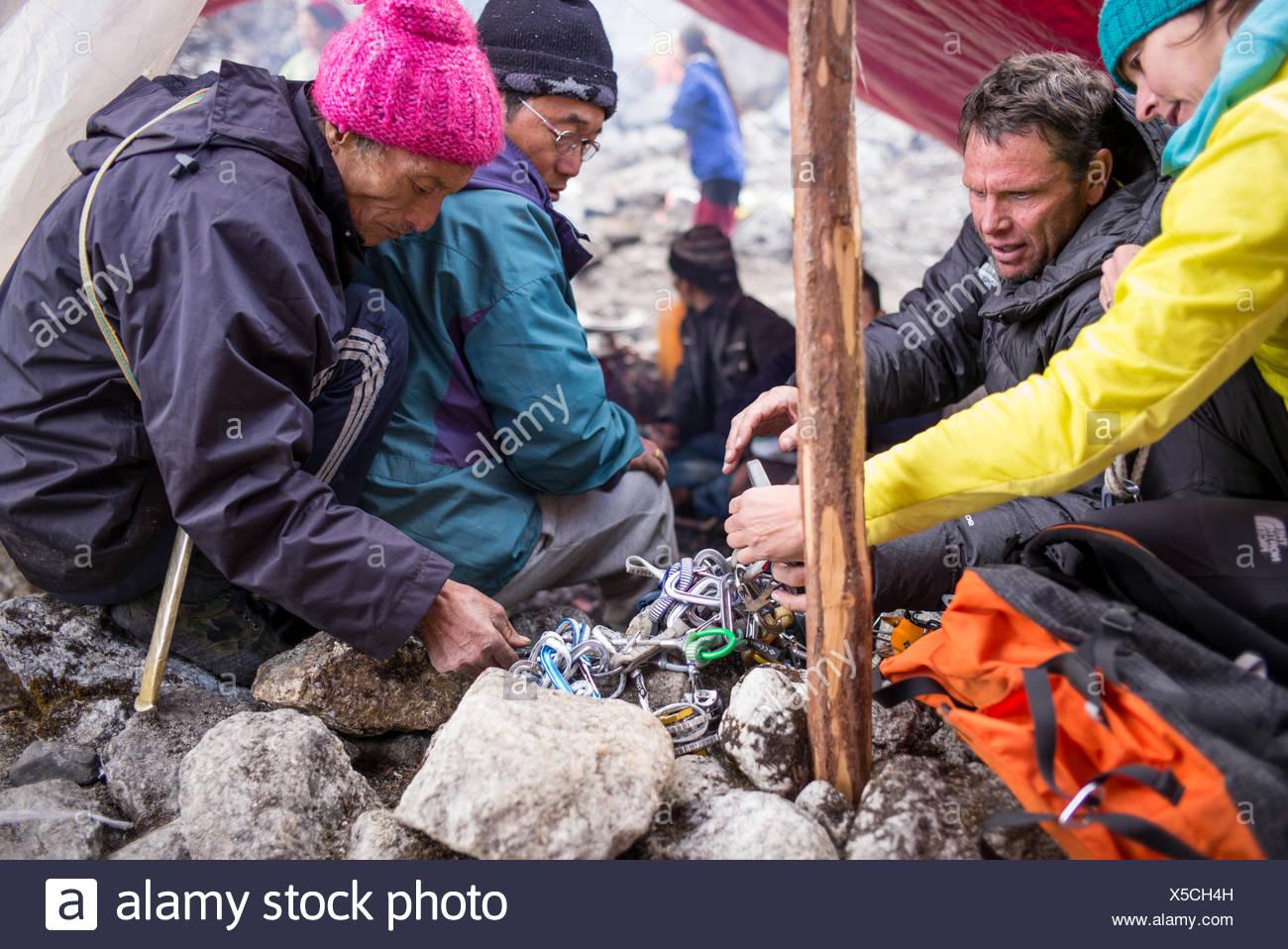 Expeditionsteilnehmer prüfen Geräte mit Hilfe von lokalen Guides. Stockfoto
