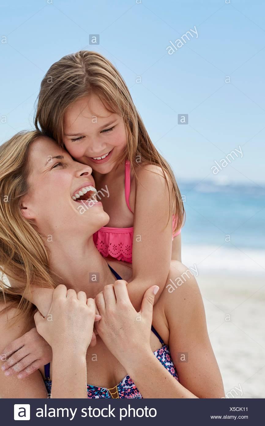 -MODELL VERÖFFENTLICHT. Mutter und Tochter am Strand lachen. Stockbild
