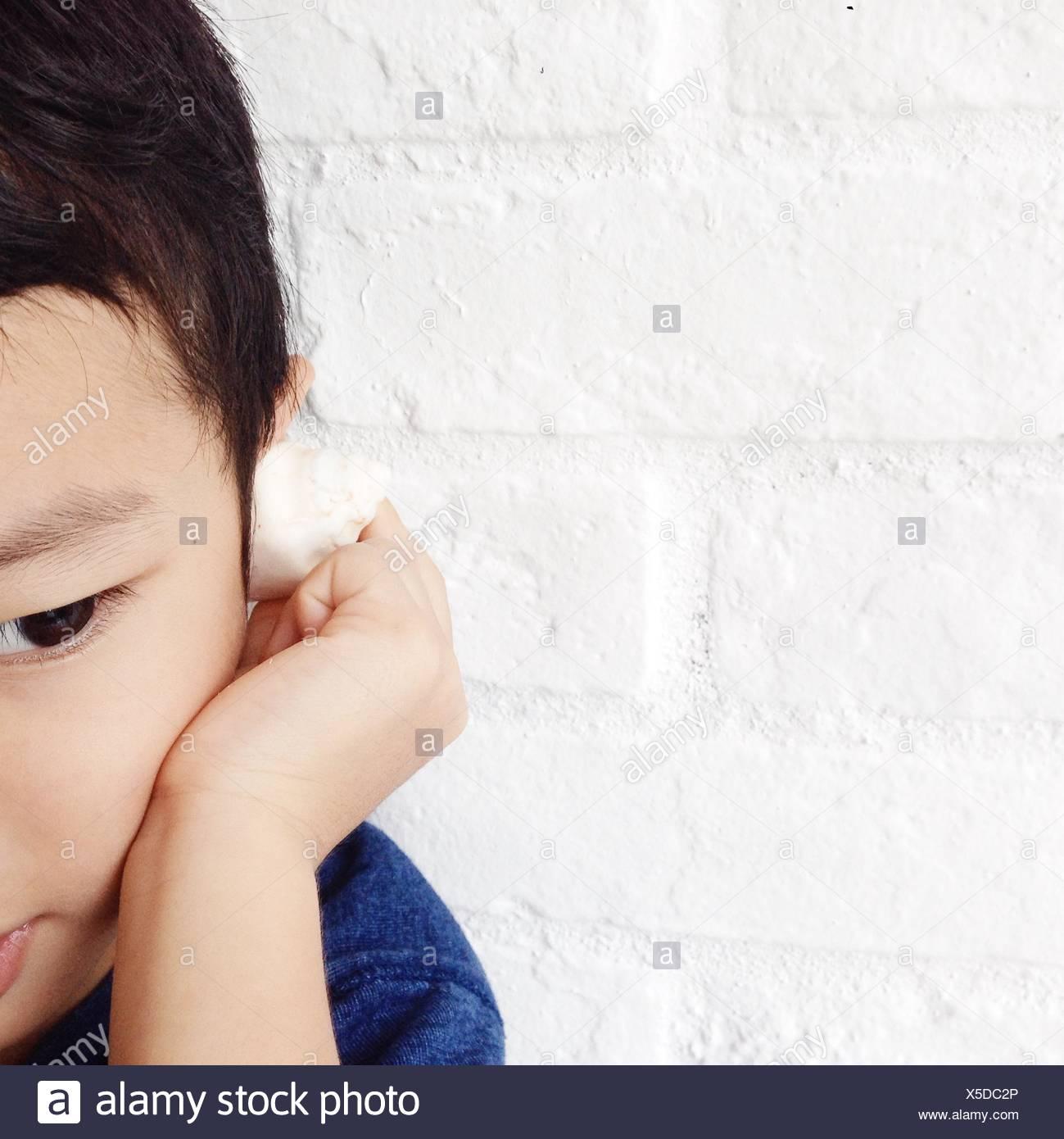 Junge hören das Meer in einer kleinen Muschel Stockbild