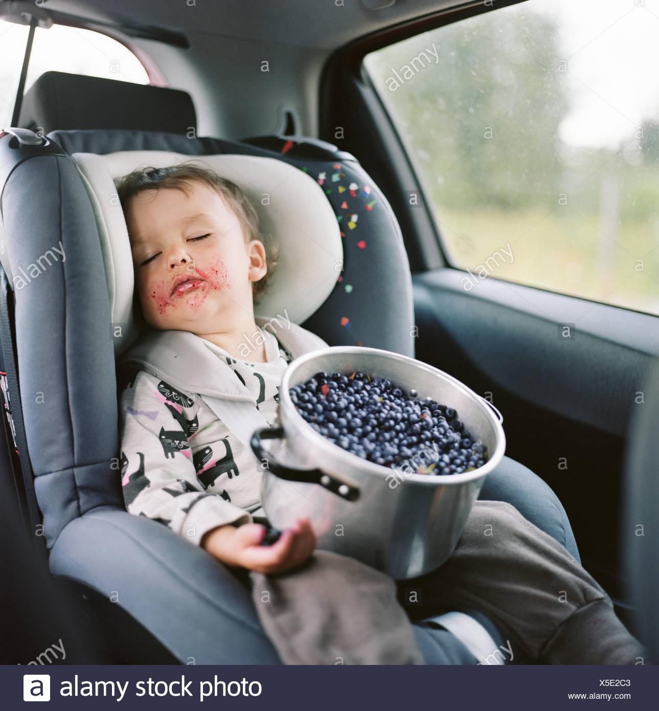 Finnland, Uusimaa, Lapinjarvi, Porträt von Mädchen (2-3) im Autositz mit Topf voller Heidelbeeren auf Schoß schlafen Stockbild