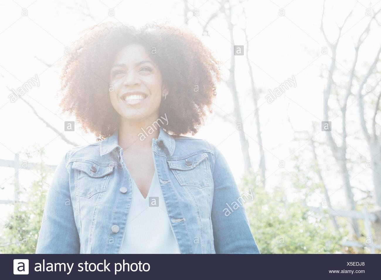 Niedrigen Winkel Ansicht Porträt Mitte erwachsenen Frau im Sonnenlicht, Lächeln, wegschauen Stockbild