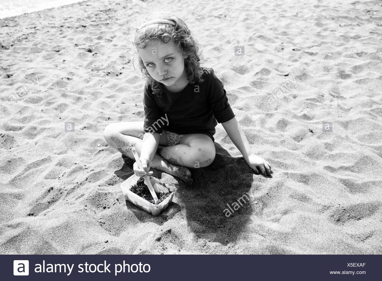 Traurig aussehende Mädchen sitzen am Strand, Italien Stockbild