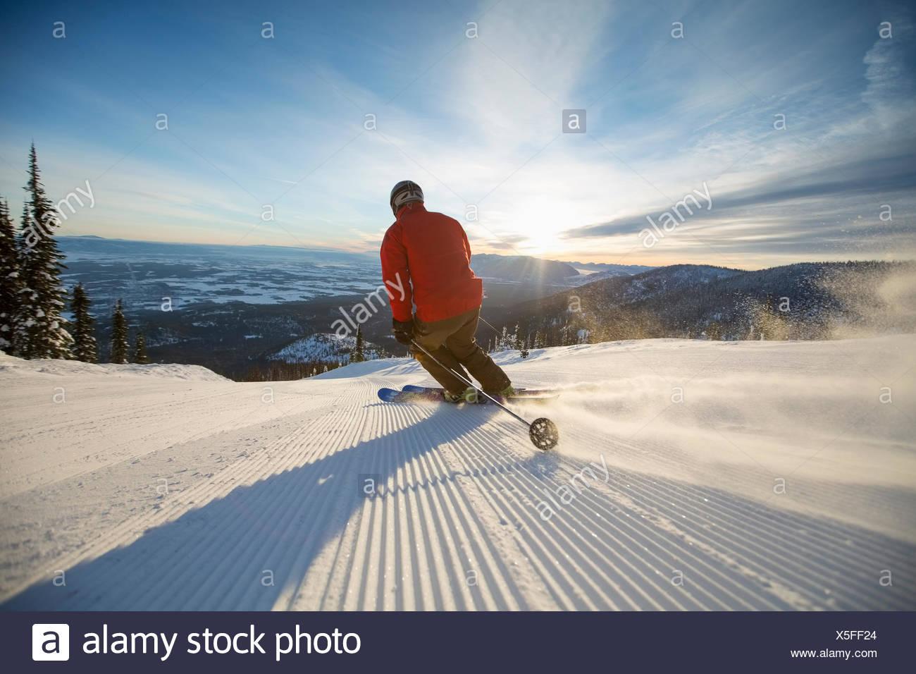 Reifer Mann auf Skipiste bei Sonnenuntergang Stockbild