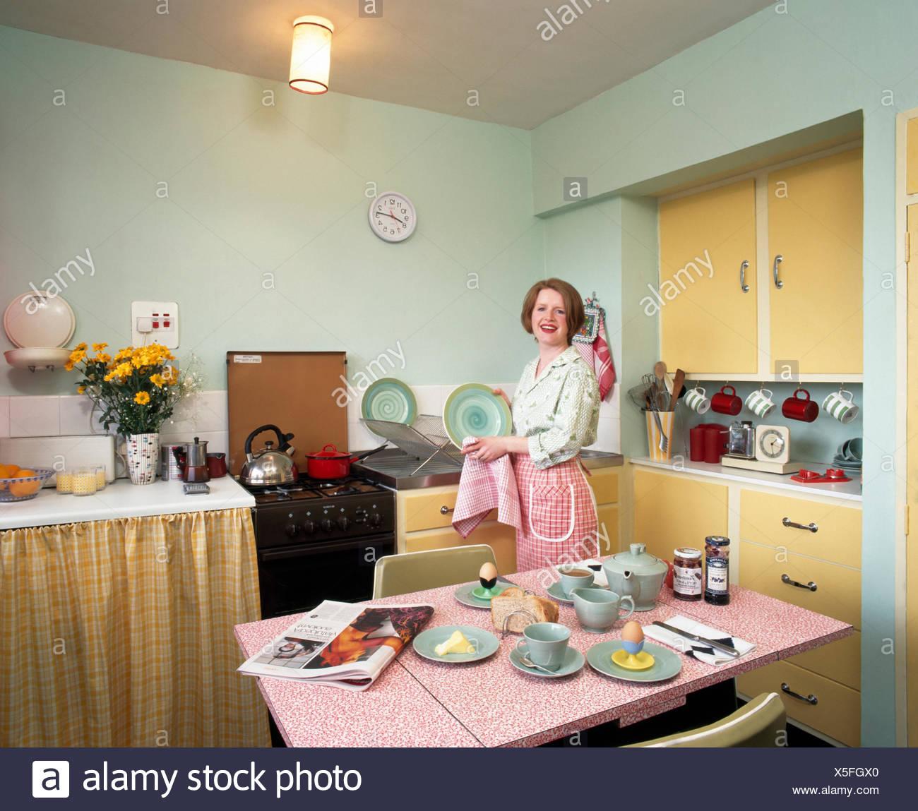 Porträt einer jungen Frau, die Trocknung Gerichte in neunziger Jahre, Wirtschaft Küche für nur zur redaktionellen Nutzung Stockbild