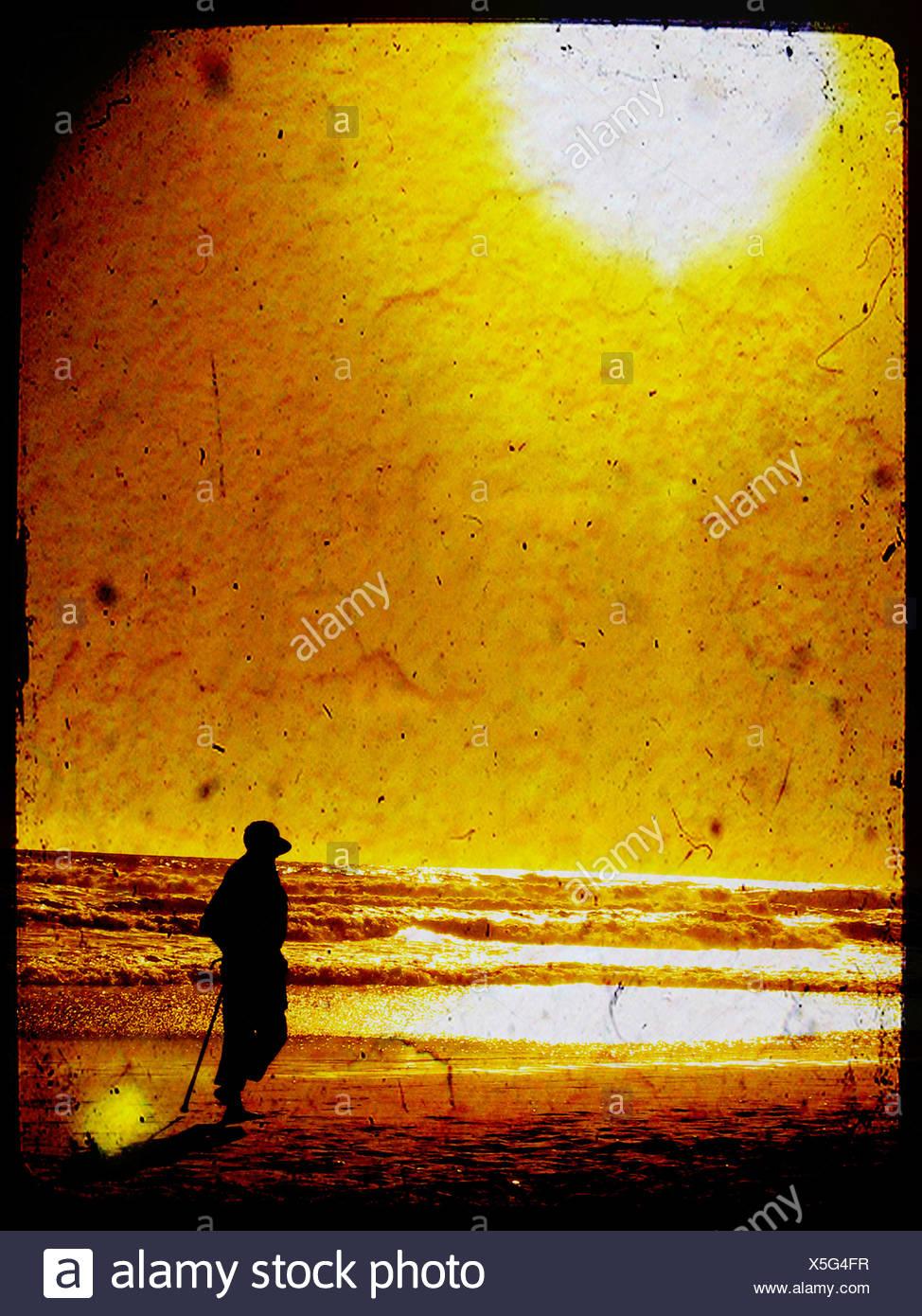 Die Silhouette einer Erwachsenen-Figur am Strand mit einer untergehenden Sonne Stockbild