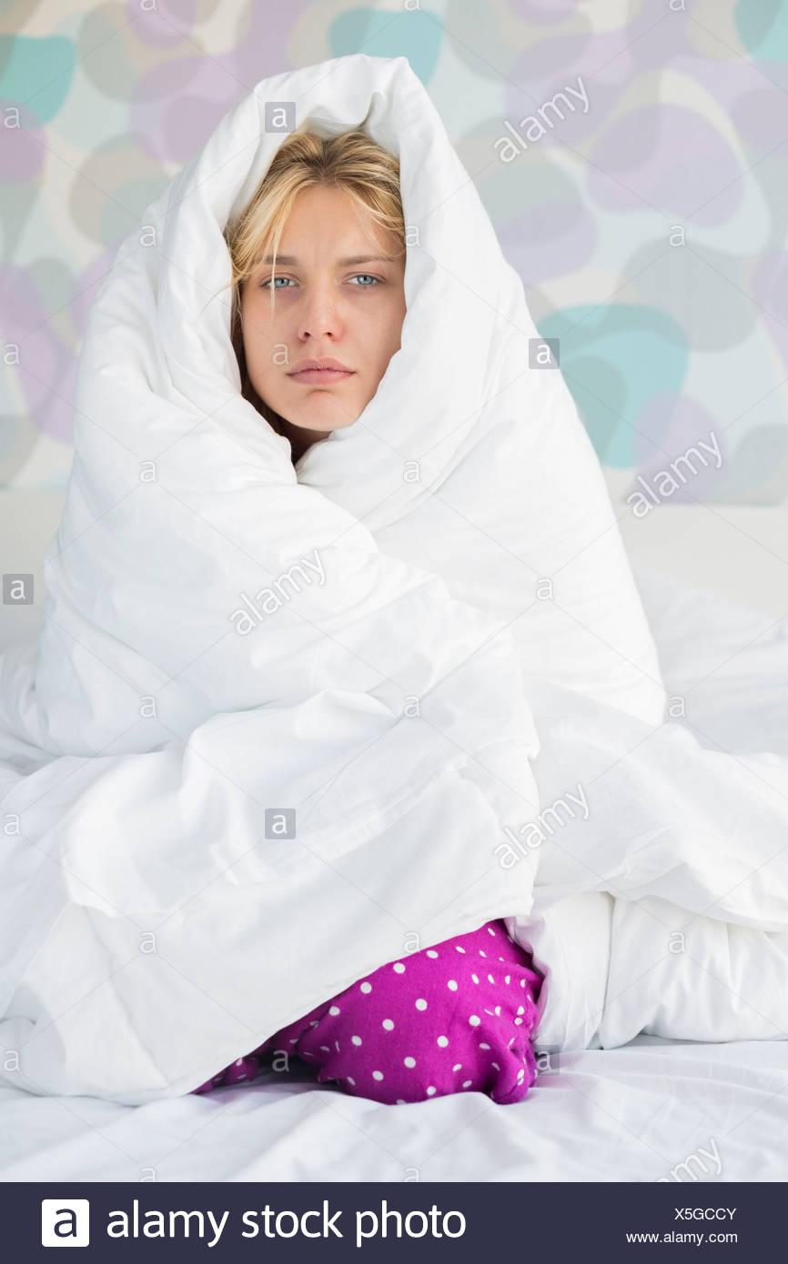 Porträt der jungen Frau leidet Fieber während umhüllt von Quilt im Bett Stockbild